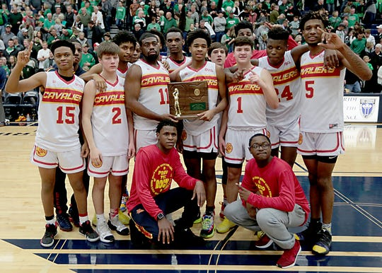 Purcell Marian boys basketball celebrates with their trophy after their Division III regional final victory over Anna at Trent Arena in Kettering Saturday, Mar. 16, 2019.