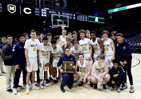 The Moeller Crusaders pose with their Regional Championship Trophy in the boys regional final against Centerville at the Cintas Center at Xavier University. Moeller defeated Centerville 59-41 and will move on to the Final Four in Columbus.