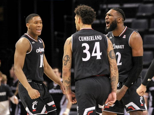 Cincinnati's Rashawn Fredericks (10), Jarron Cumberland (34) and Eliel Nsoseme (22) celebrate during the second half of Sunday's AAC Tournament championship game against Houston at FedExForum.