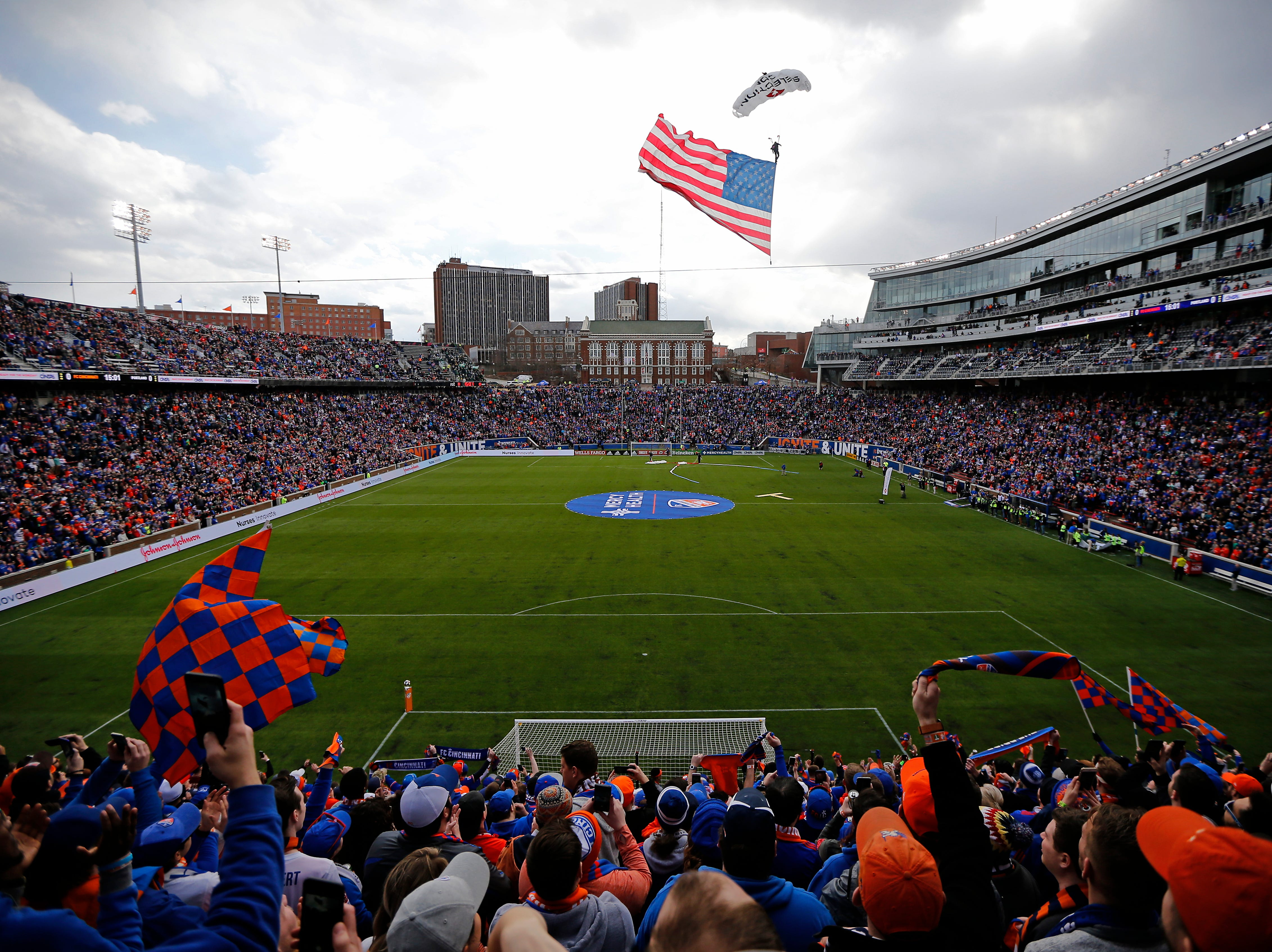 Skydivers deliver the American Flag before the first half of the MLS match between FC Cincinnati and the Portland Timbers at Nippert Stadium in Cincinnati on Sunday, March 17, 2019. FC Cincinnati led 1-0 at halftime.