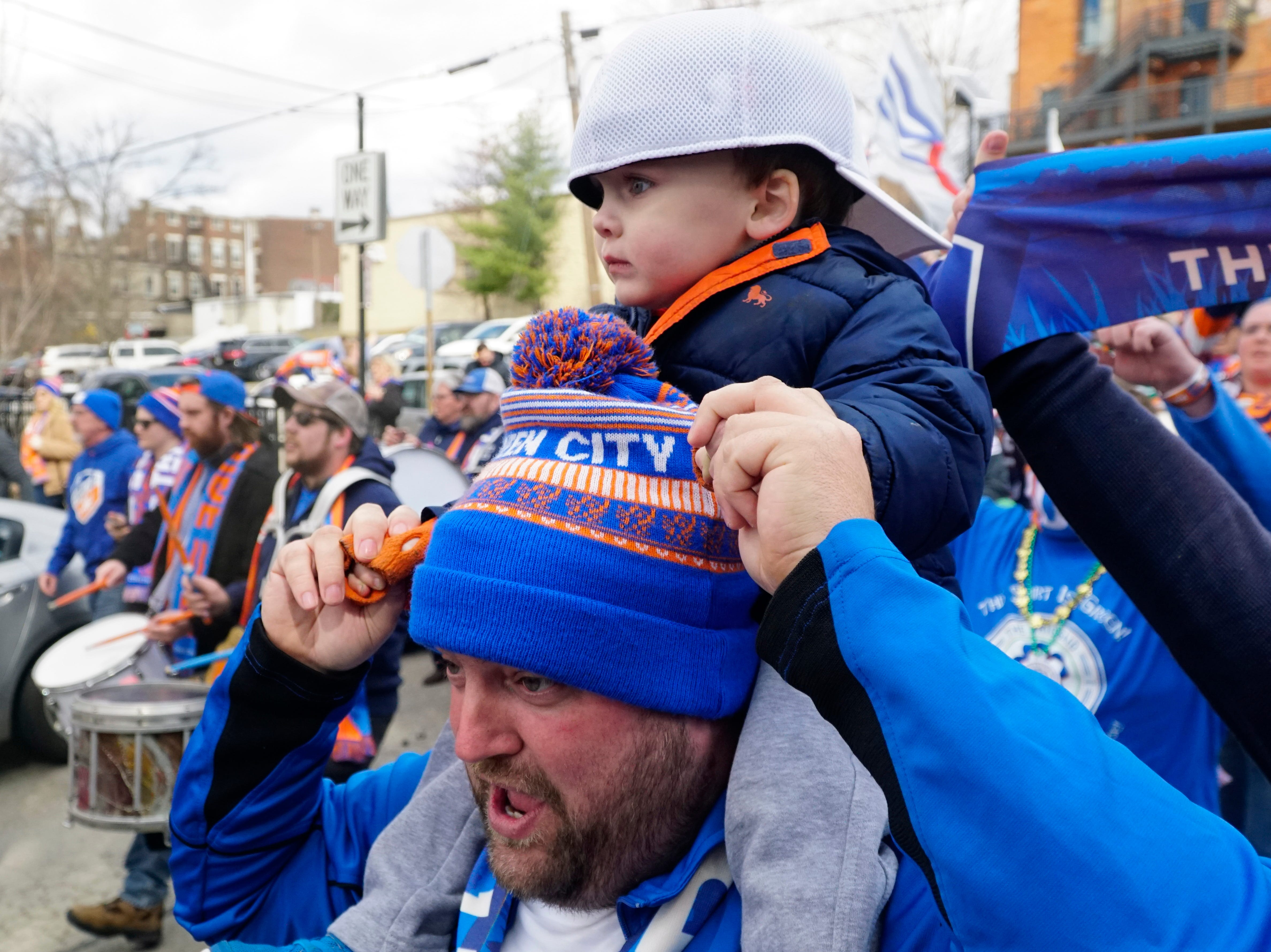 Ryan Sparks carries his son Parker, age two, ahead of a crush of FC Cincinnati fans headed to the first FCC home game against Portland at Nippert Stadium, March 17, 2019.