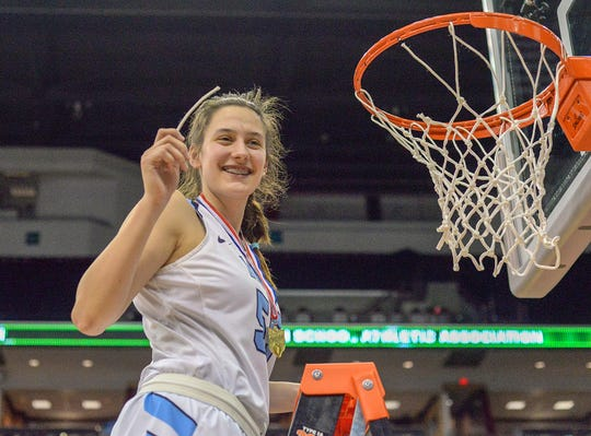 Julia Hoefling of Mount Notre Dame smiles as she shows a peice of net after beating Pickerington Central in the OHSAA Division I Championship at the Shottenstein Center in Columbus, OH, Saturday, March 16, 2019