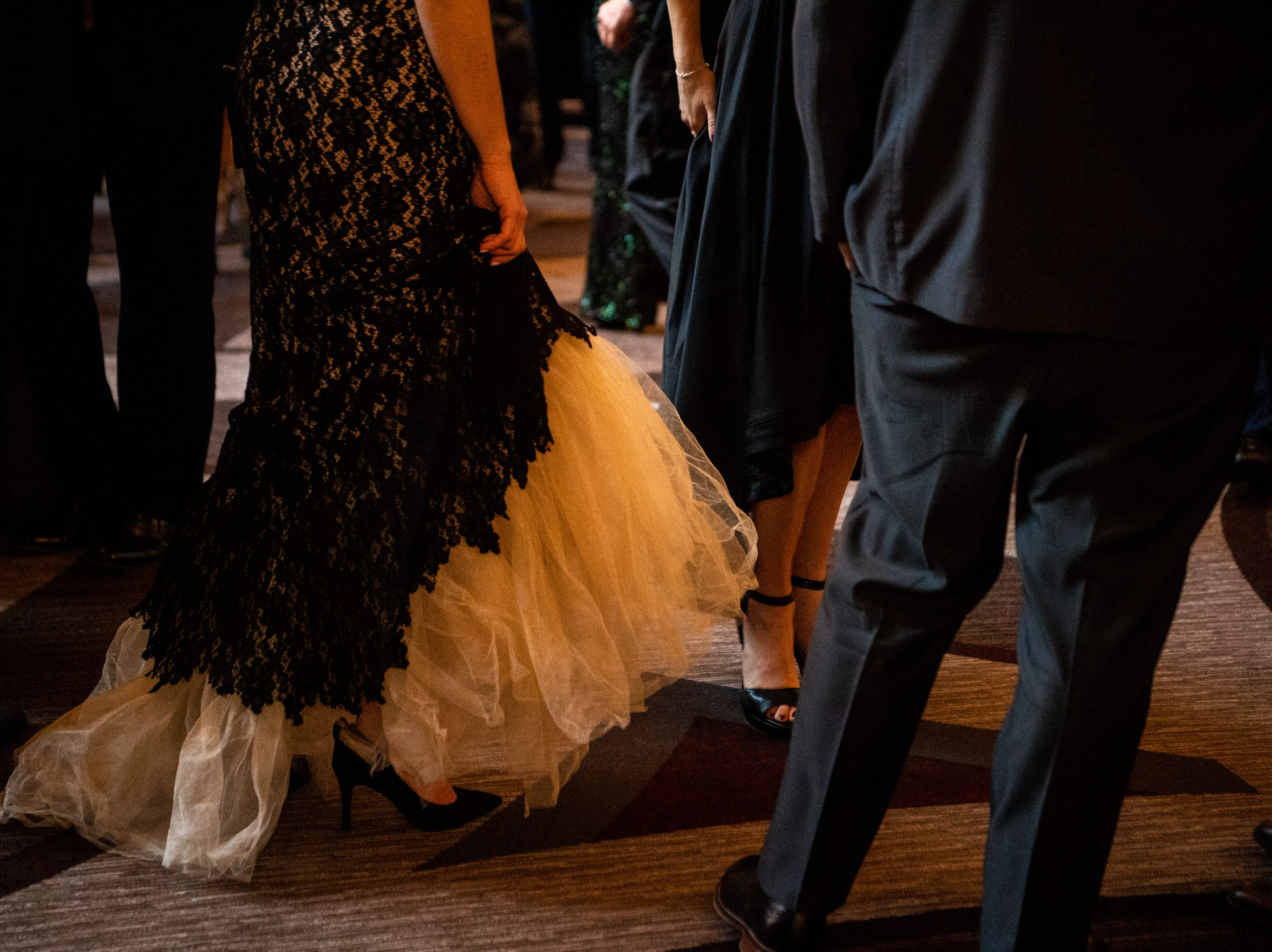 A woman holds her dress as she walks during Austin Peay State University's annual Candlelight Ball at the Omni Nashville Hotel Saturday, March 16, 2019, in Nashville, Tenn.