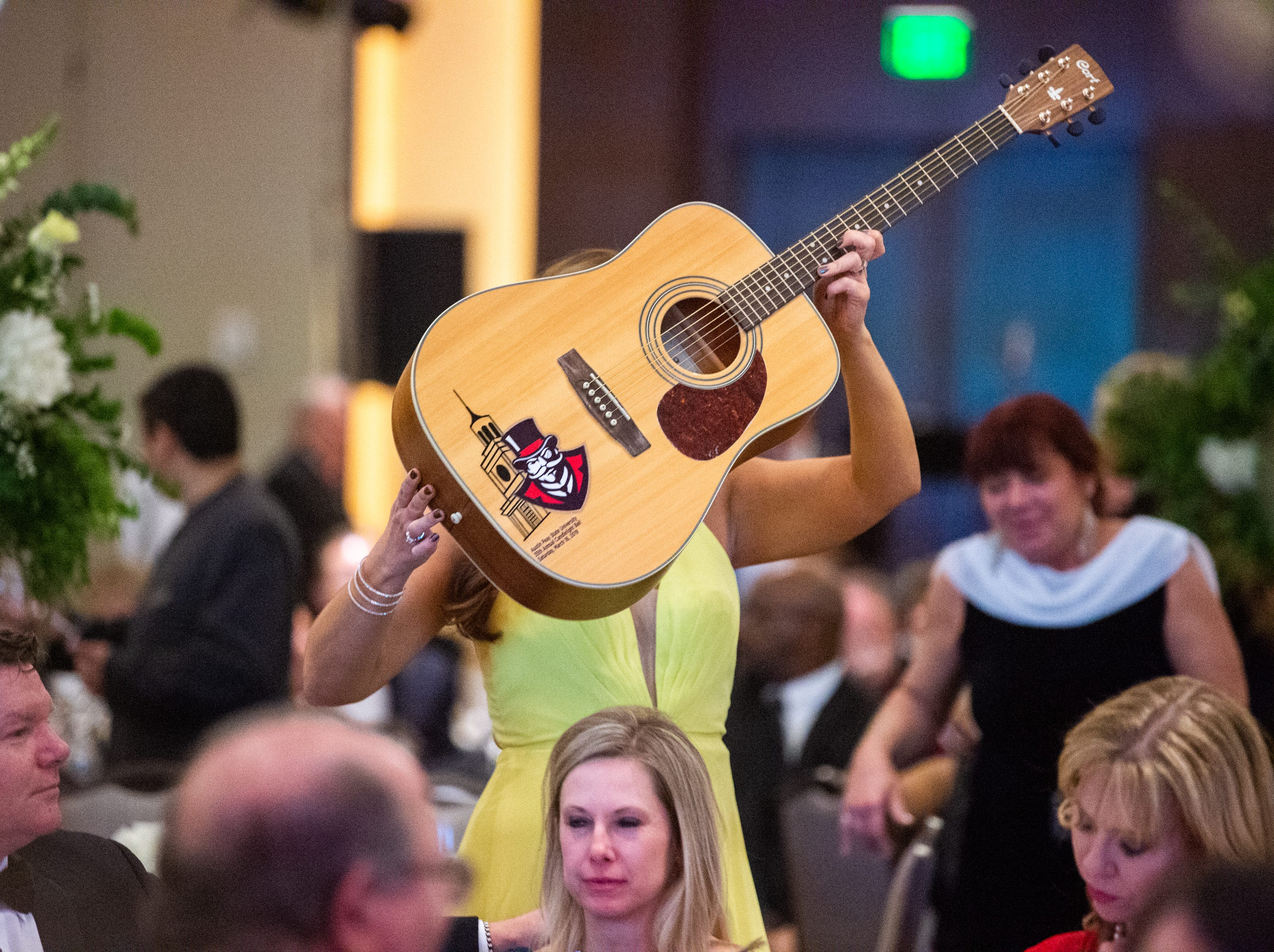 A decorated guitar is showcased for auction during Austin Peay State University's annual Candlelight Ball at the Omni Nashville Hotel Saturday, March 16, 2019, in Nashville, Tenn.