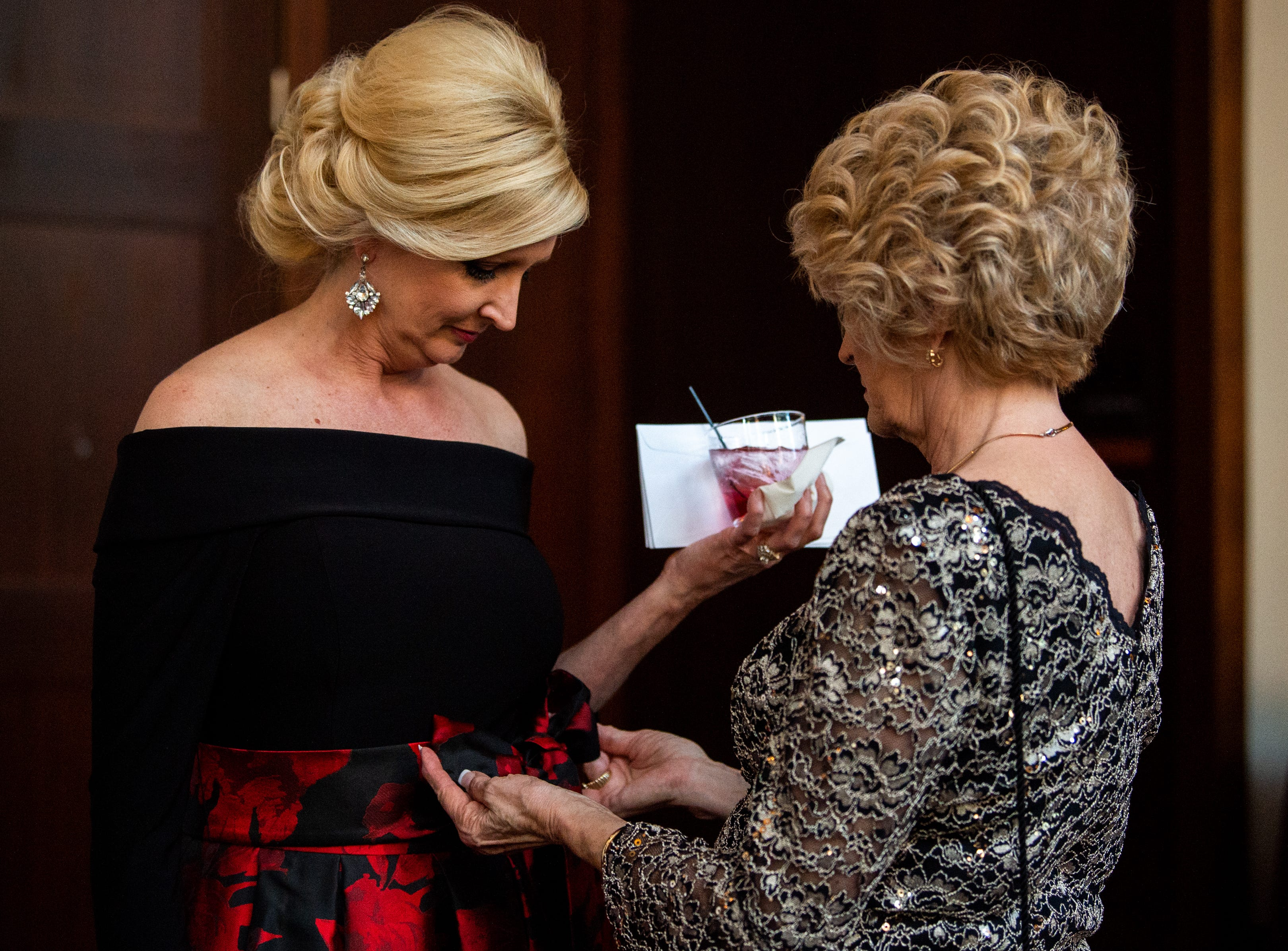 Co-chair Andrea Herrera receives help with her bow during Austin Peay State University's annual Candlelight Ball at the Omni Nashville Hotel Saturday, March 16, 2019, in Nashville, Tenn.