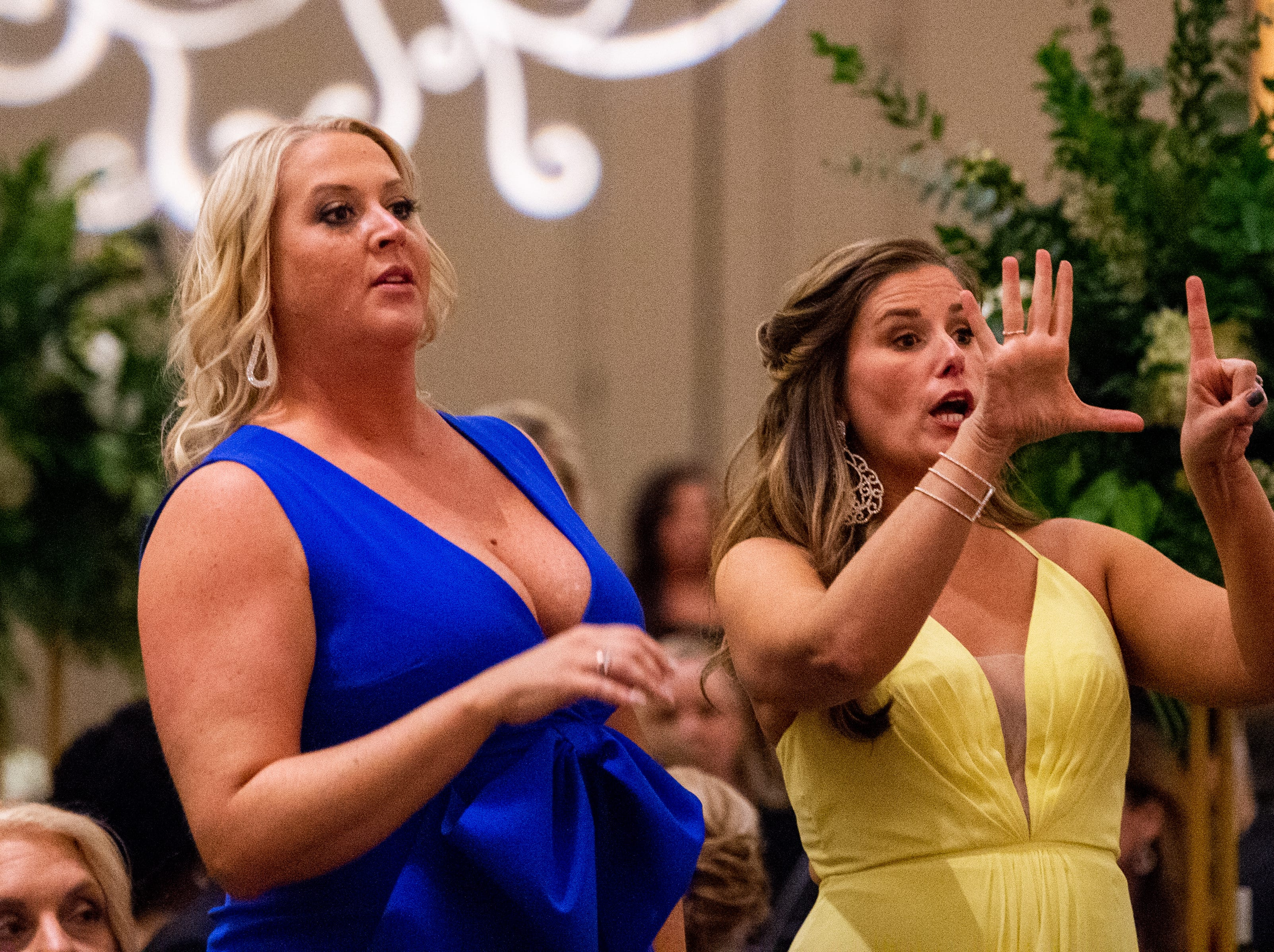 People communicate bids for the custom-designed diamond necklace made for the night during Austin Peay State University's annual Candlelight Ball at the Omni Nashville Hotel Saturday, March 16, 2019, in Nashville, Tenn.