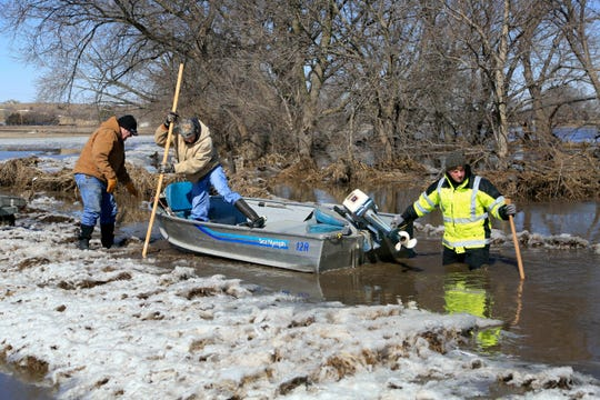 Tom Wilke, left, his son Chad, center, and Nick Kenny, launch a boat into the swollen waters of the North Fork of the Elkhorn River, to check on Witke's flooded property, in Norfolk, Neb., Friday, March 15, 2019. Heavy rain falling atop deeply frozen ground has prompted evacuations along swollen rivers in Wisconsin, Nebraska and other Midwestern states. Thousands of people have been urged to evacuate along eastern Nebraska rivers as a massive late-winter storm has pushed streams and rivers out of their banks throughout the Midwest.