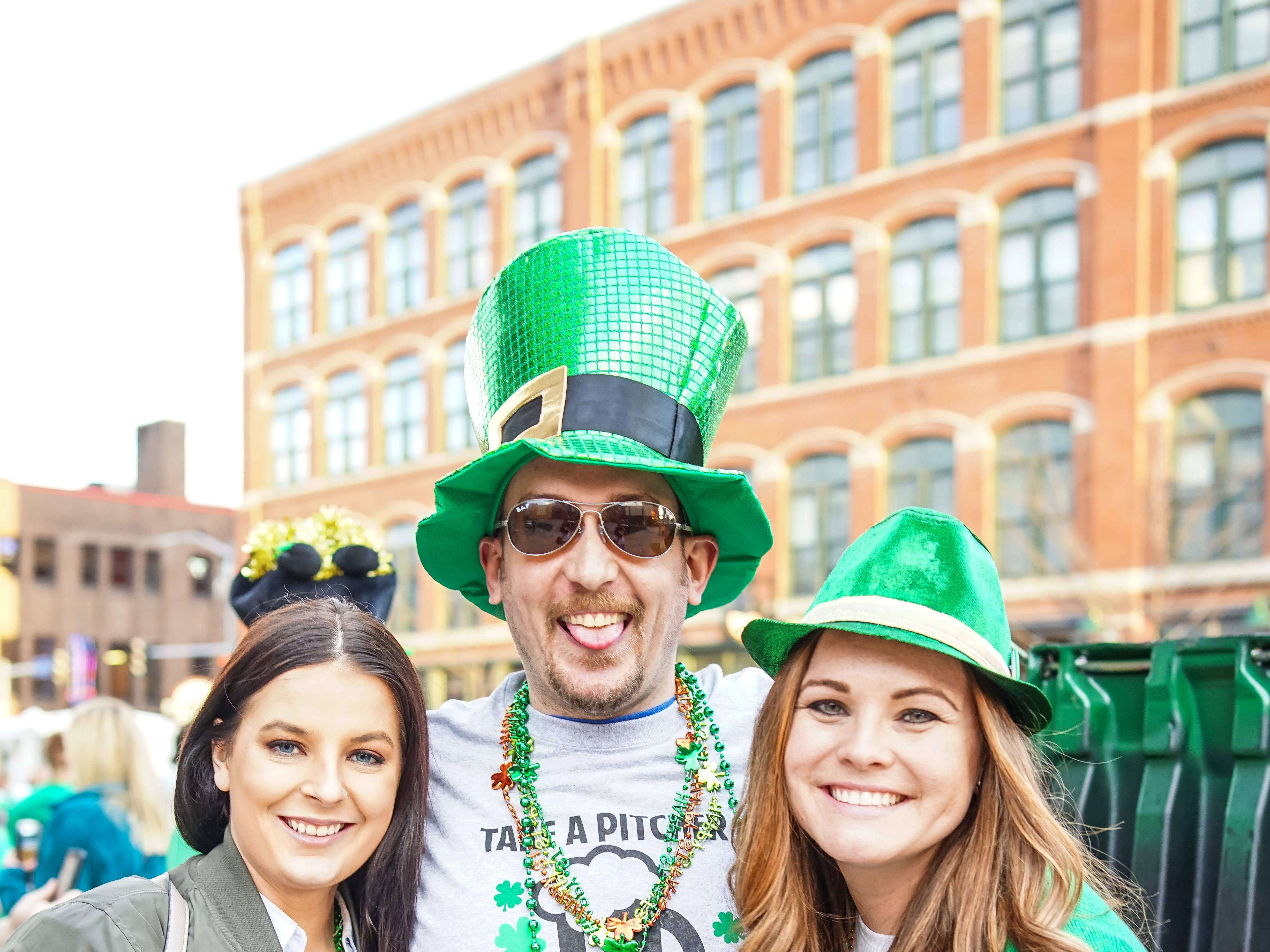 Christina Midlang, 23, Jason Stewart, 31, and Laura Stewart, 32, all of Des Moines, celebrating the holiday, Saturday, March 16, 2019, at the Court Avenue Block Party.