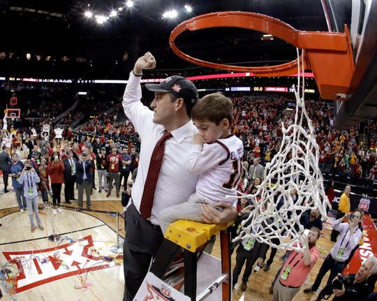 Iowa State coach Steve Prohm holds his son Cass, 4, as he cuts the net after Iowa State defeated Kansas 78-66 in an NCAA college basketball game to win the Big 12 men's tournament Saturday, March 16, 2019, in Kansas City, Mo. (AP Photo/Charlie Riedel)