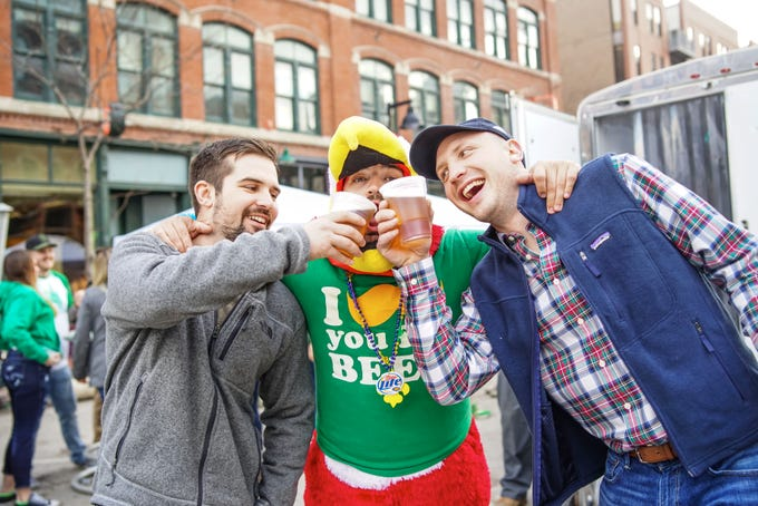 Jake Sargent, 26, Matt Knipp, 26, and Joe Hanson, 26, all of Des Moines, celebrating Saint Patrick's day, Saturday, March 16, 2019, at the Court Avenue Block Party.