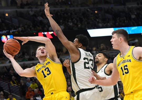 Mar 17, 2019; Chicago, IL, USA; Michigan Wolverines forward Ignas Brazdeikis (13) Michigan State Spartans forward Xavier Tillman (23) during the first half in the Big Ten conference tournament at United Center. Mandatory Credit: David Banks-USA TODAY Sports