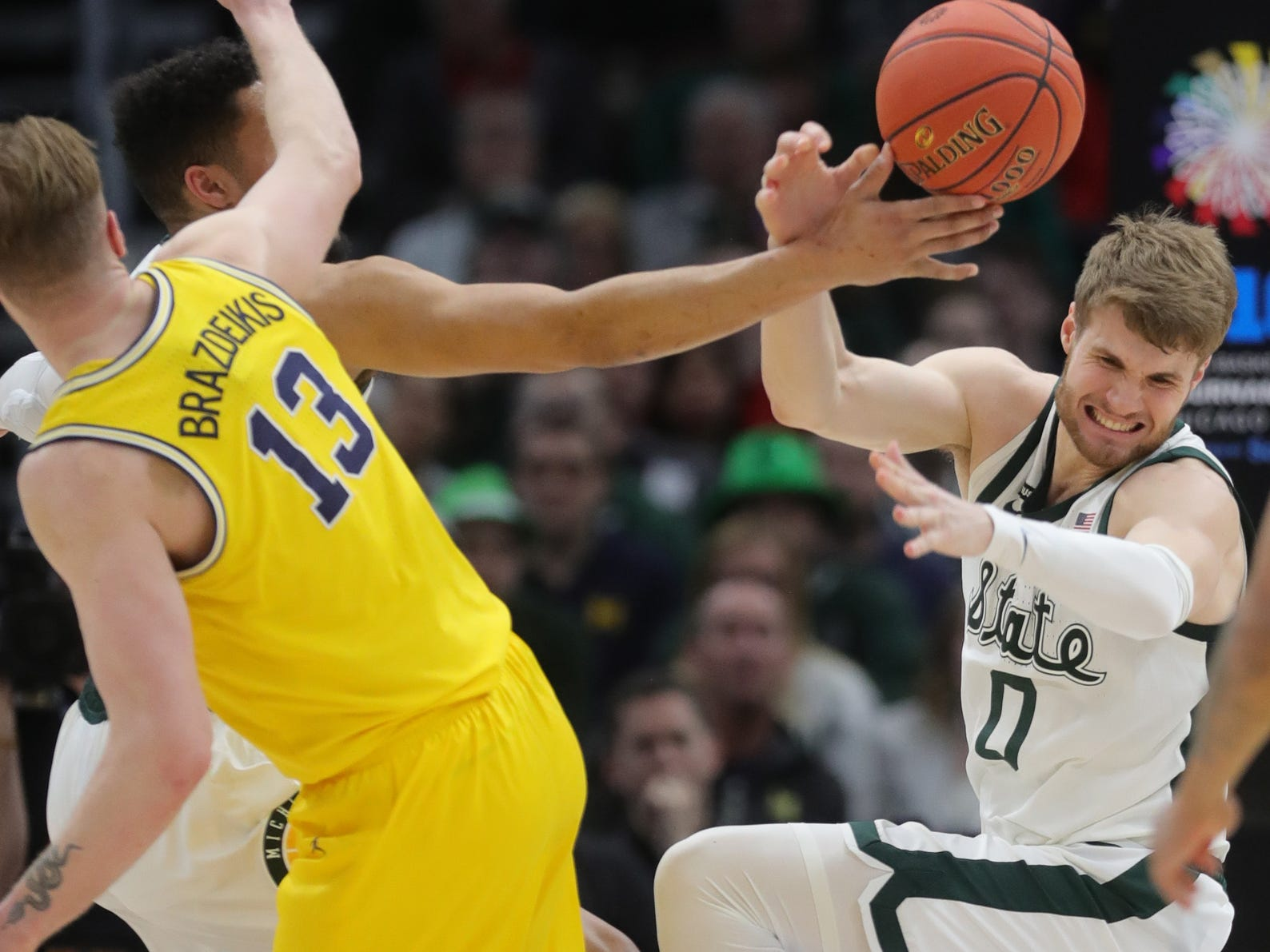 Michigan State's Kyle Ahrens rebounds against Michigan's Ignas Brazkeikis during the first half of the Big Ten tournament championship Sunday, March 17, 2019 at the United Center in Chicago.