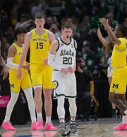 Matt McQuaid celebrates after a basket against Michigan during the second half in Chicago.