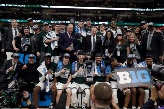 Michigan State players and coaches pose with the championship trophy after defeating Michigan 65-60 in an NCAA college basketball championship game in the Big Ten Conference tournament, Sunday, March 17, 2019, in Chicago. (AP Photo/Nam Y. Huh)