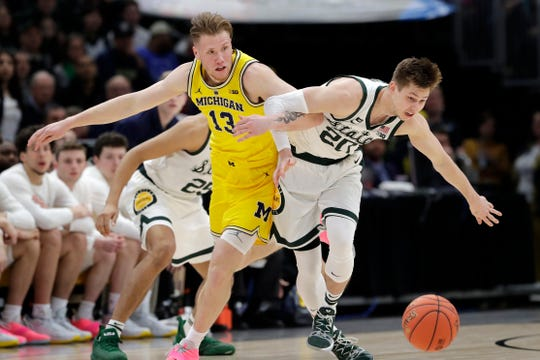Michigan State's Matt McQuaid and Michigan's Ignas Brazdeikis battle for a loose ball during the first half of the Big Ten tournament title game, Sunday, March 17, 2019, in Chicago.