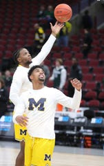 Michigan guards Zavier Simpson, top, and David DeJulius warm up before the Big Ten tournament championship against Michigan State, Sunday, March 17, 2019 at the United Center in Chicago.