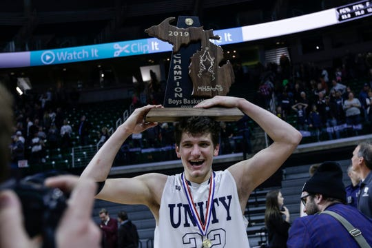 Hudsonville Unity Christian's T.J. VanKoevering (32) puts the championship trophy on his head and walks off the court after the Crusaders defeated River Rouge 58-55 at the MHSAA Division 2 final at the Breslin Center in East Lansing, Saturday, March 16, 2019.