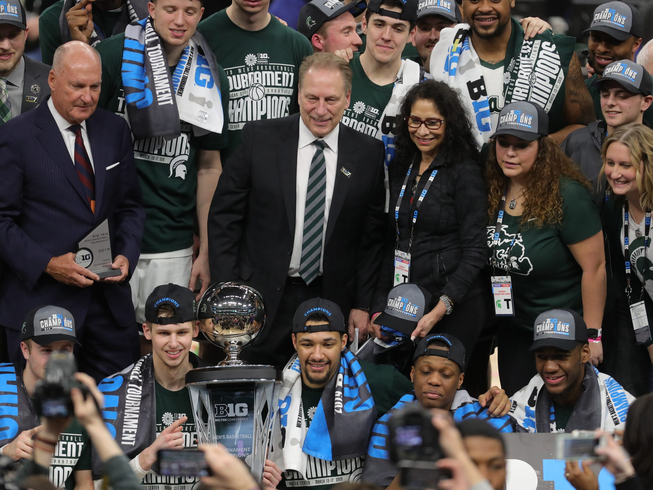 Tom Izzo, wife Lupe Izzo, and Michigan State players and coaches pose with the Big Ten tournament championship trophy after defeating Michigan, 65-60,  Sunday, March 17, 2019 at the United Center in Chicago.