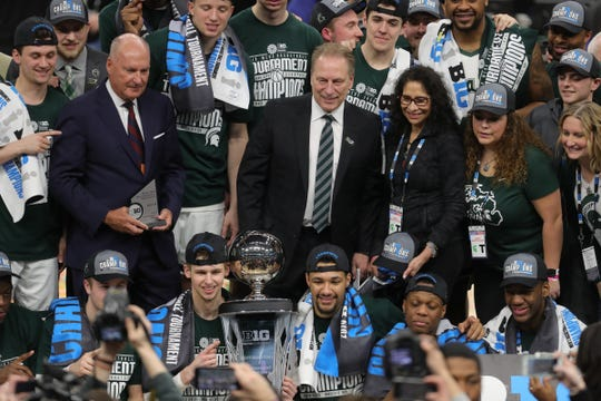 Tom Izzo, wife Lupe, and MSU players and coaches pose with the Big Ten tournament championship trophy after defeating Michigan, 65-60, Sunday.