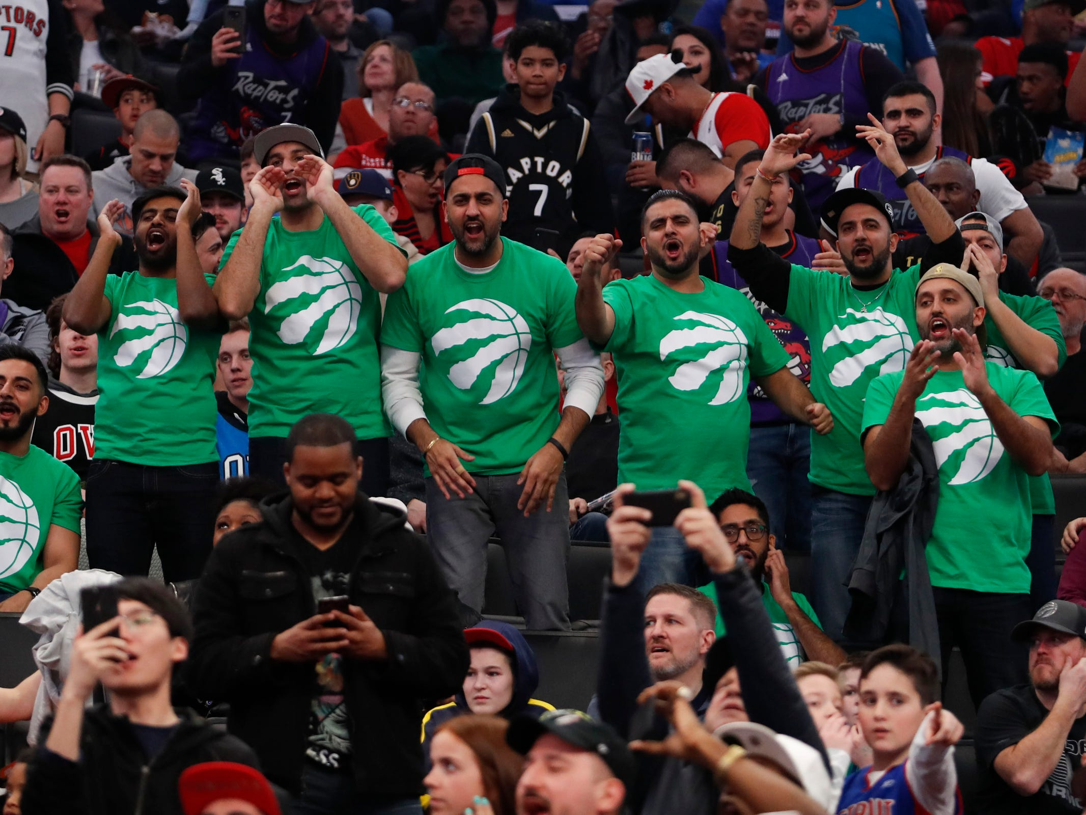 Toronto Raptors fans cheer in green shirts honoring St. Patrick's Day during the first quarter against the Detroit Pistons at Little Caesars Arena, Sunday, March 17, 2019.