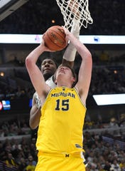Michigan Wolverines center Jon Teske (15) is defended by Michigan State Spartans forward Aaron Henry (11) during the first half in the Big Ten conference tournament at United Center.