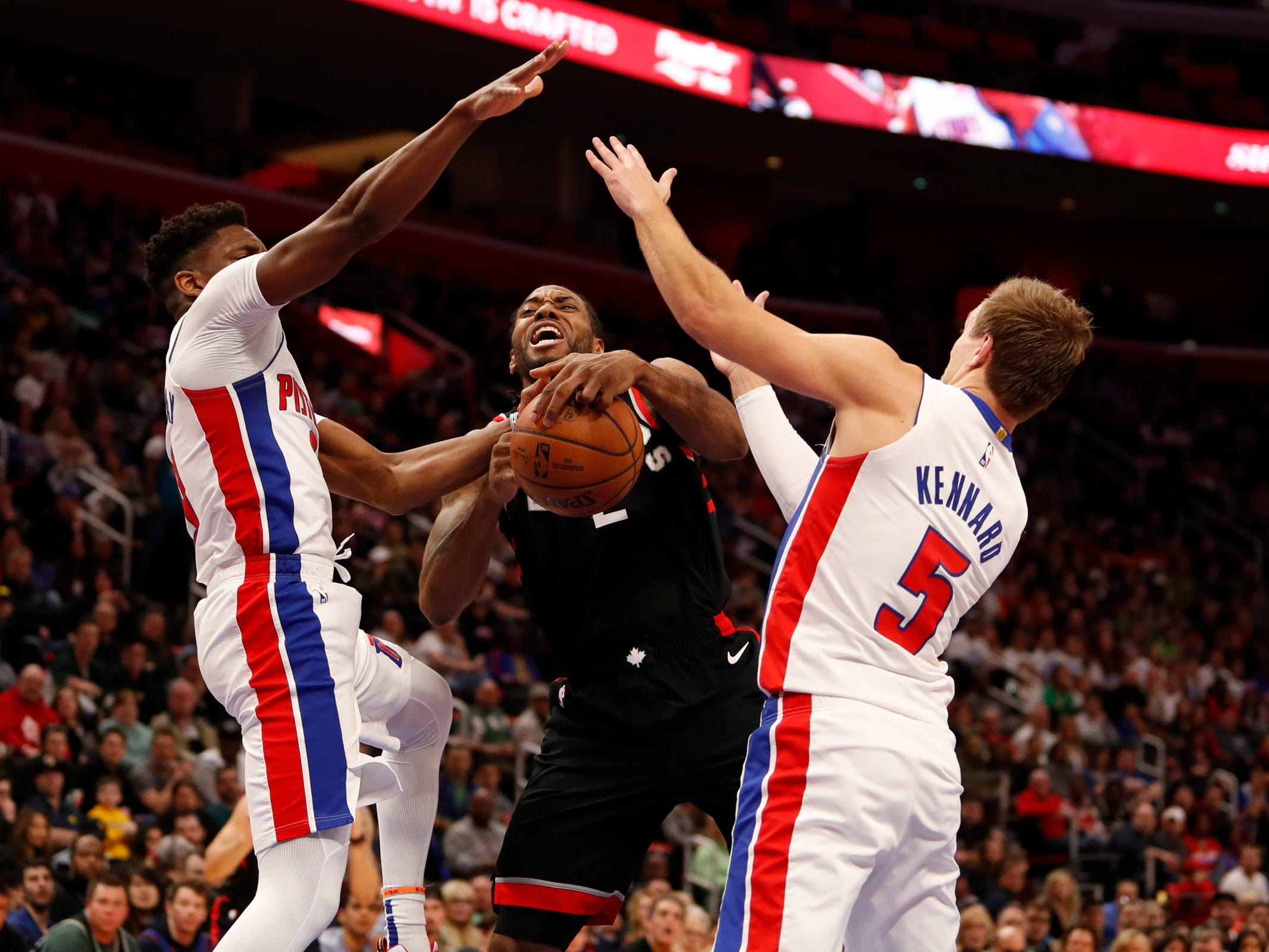 Toronto Raptors forward Kawhi Leonard is defended by Detroit Pistons guards Langston Galloway and Luke Kennard during the fourth quarter at Little Caesars Arena, Sunday, March 17, 2019.