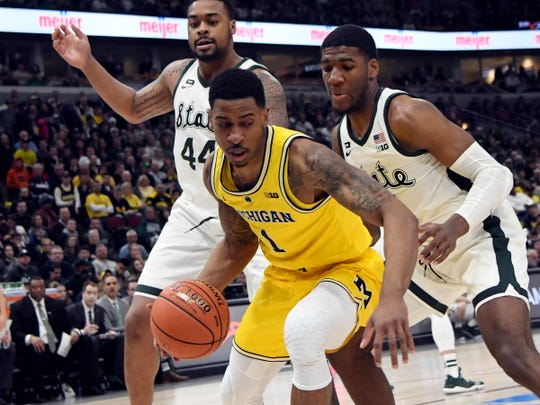 Michigan guard Charles Matthews is defended by Michigan State forwards Nick Ward (44) and Aaron Henry (11) during the first half in the Big Ten tournament title game in Chicago, March 17, 2019.