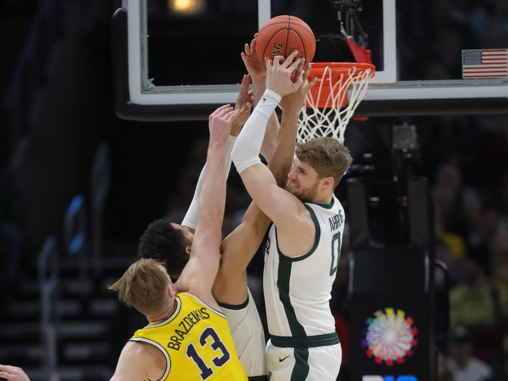 Michigan State forwards Kyle Ahrens, right, and Kenny Goins rebound against Michigan forward Ignas Brazkeikis during the first half of the Big Ten tournament championship Sunday, March 17, 2019 at the United Center in Chicago.
