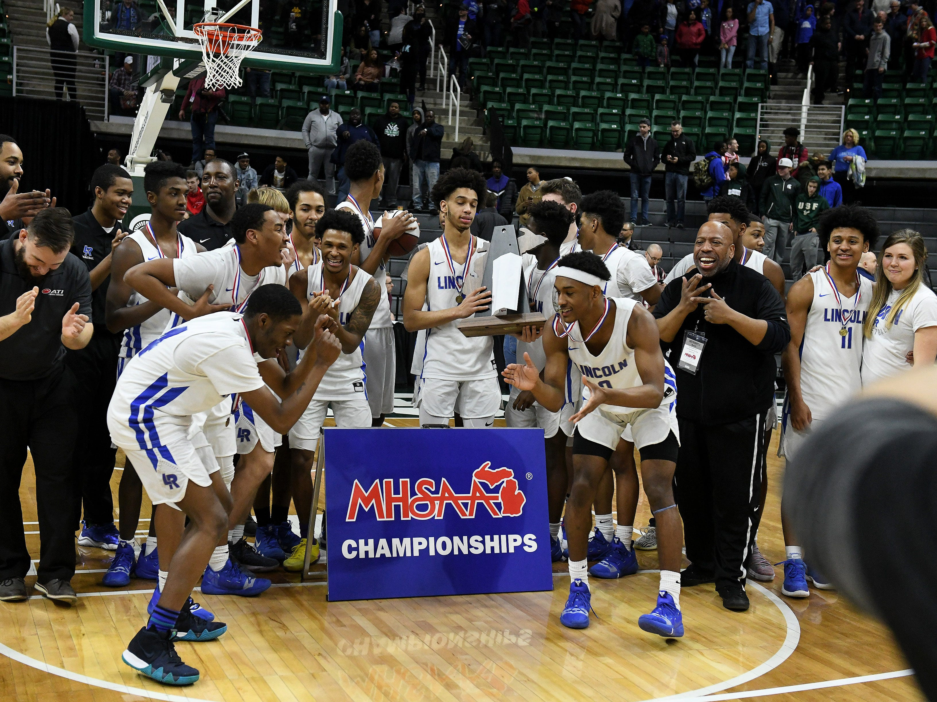 Lincoln guard Tahj Chatman (0) and Lincoln guard forward Aaron Hurling, left, dance after their team is presented with the trophy.