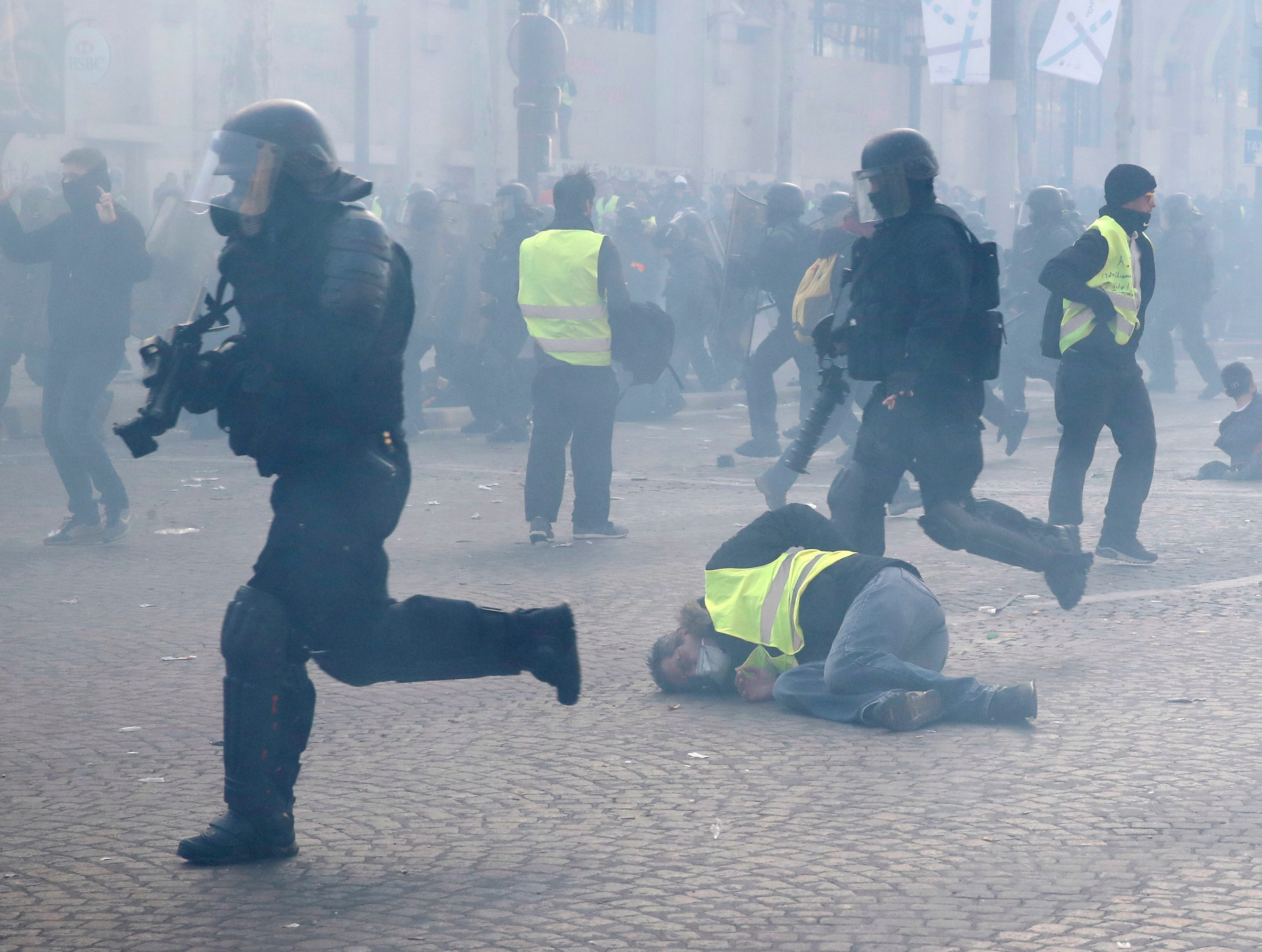 Riot police officers charge as a yellow vests demonstrator falls Saturday, March 16, 2019 in Paris. Paris police say more than 100 people have been arrested amid rioting in the French capital by yellow vest protesters and clashes with police. They set life-threatening fires, smashed up luxury stores and clashed with police firing tear gas and water cannon