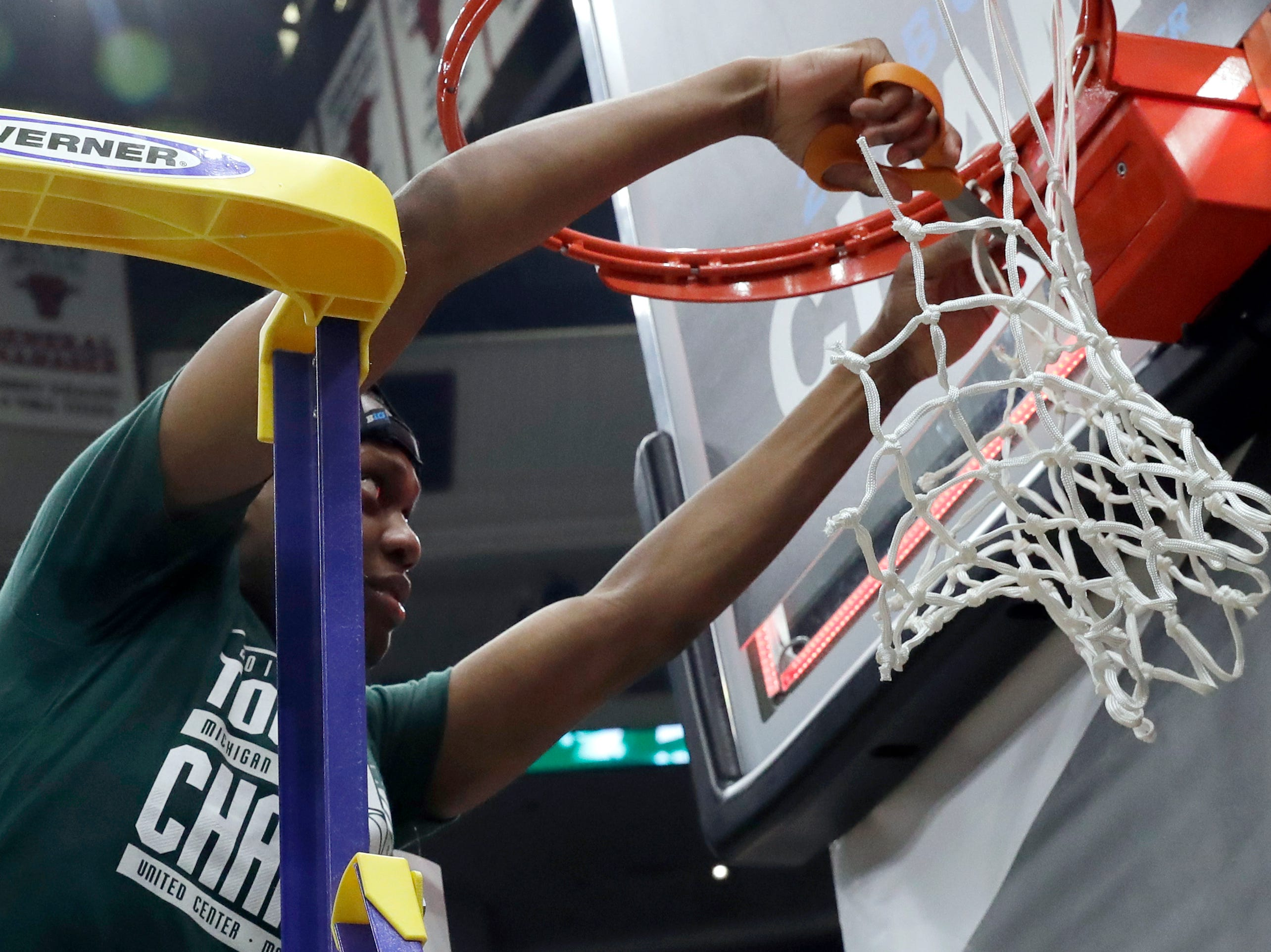 Michigan State's Cassius Winston (5) cuts a piece of the net after defeating Michigan 65-60.