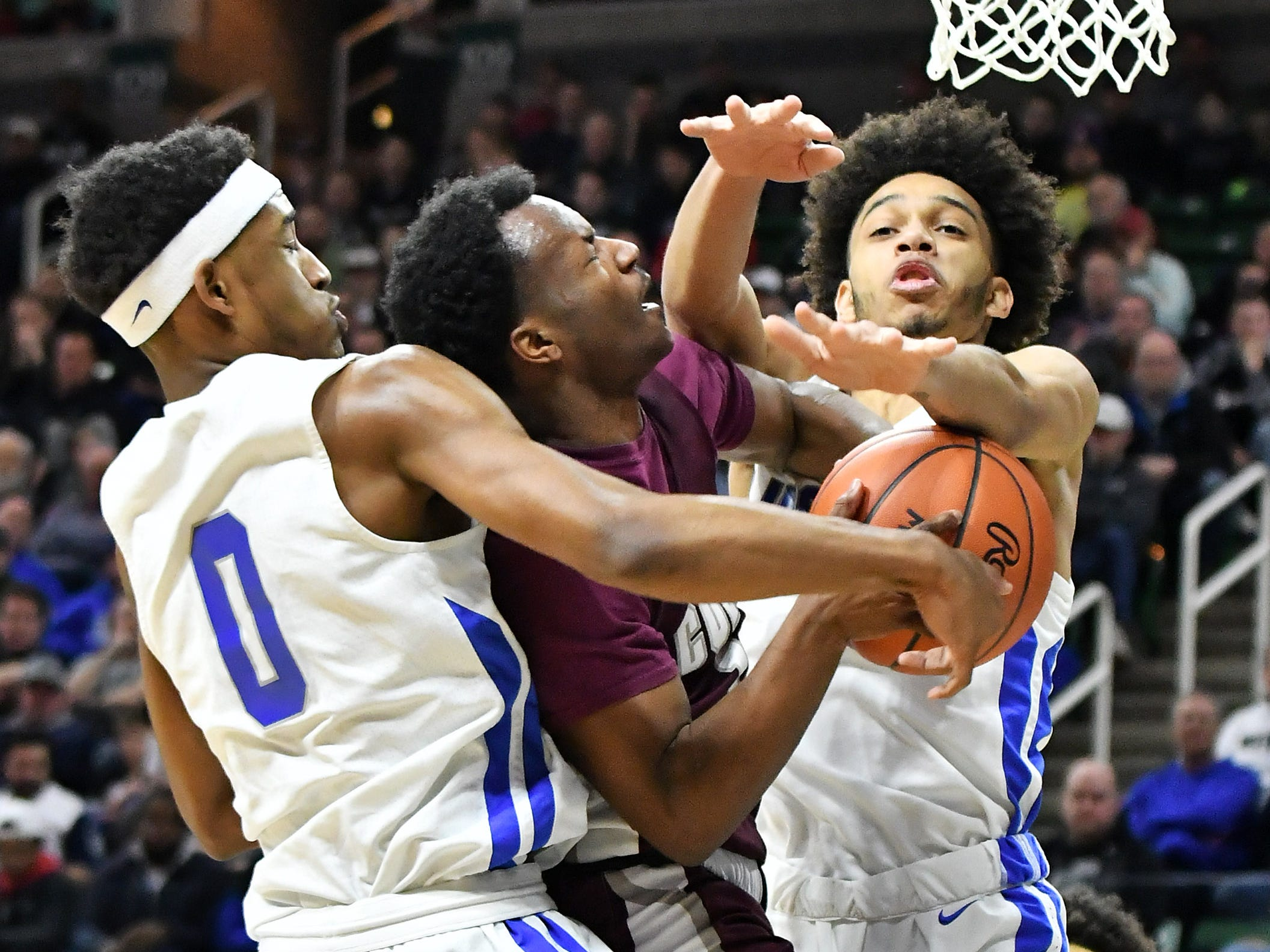 Lincoln guard Tahj Chatman (0) and Lincoln guard Amari Frye (4) converge on U-D Jesuit's Julian Dozier (1) in the second half.