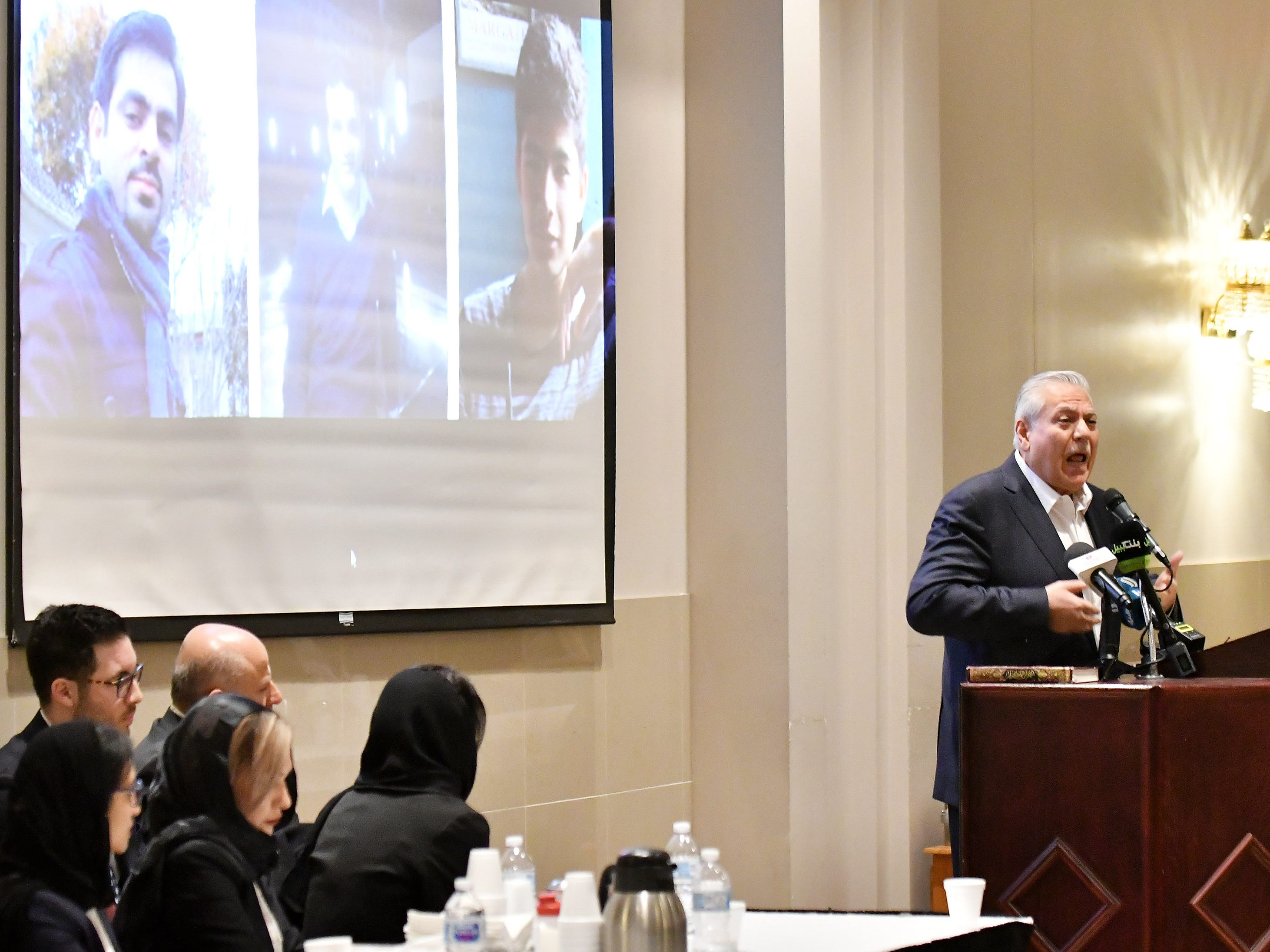 Osama Siblani, publisher of The Arab American News, speaks at the memorial.  On the screen are photos of the victims from the New Zealand mosque shooting.