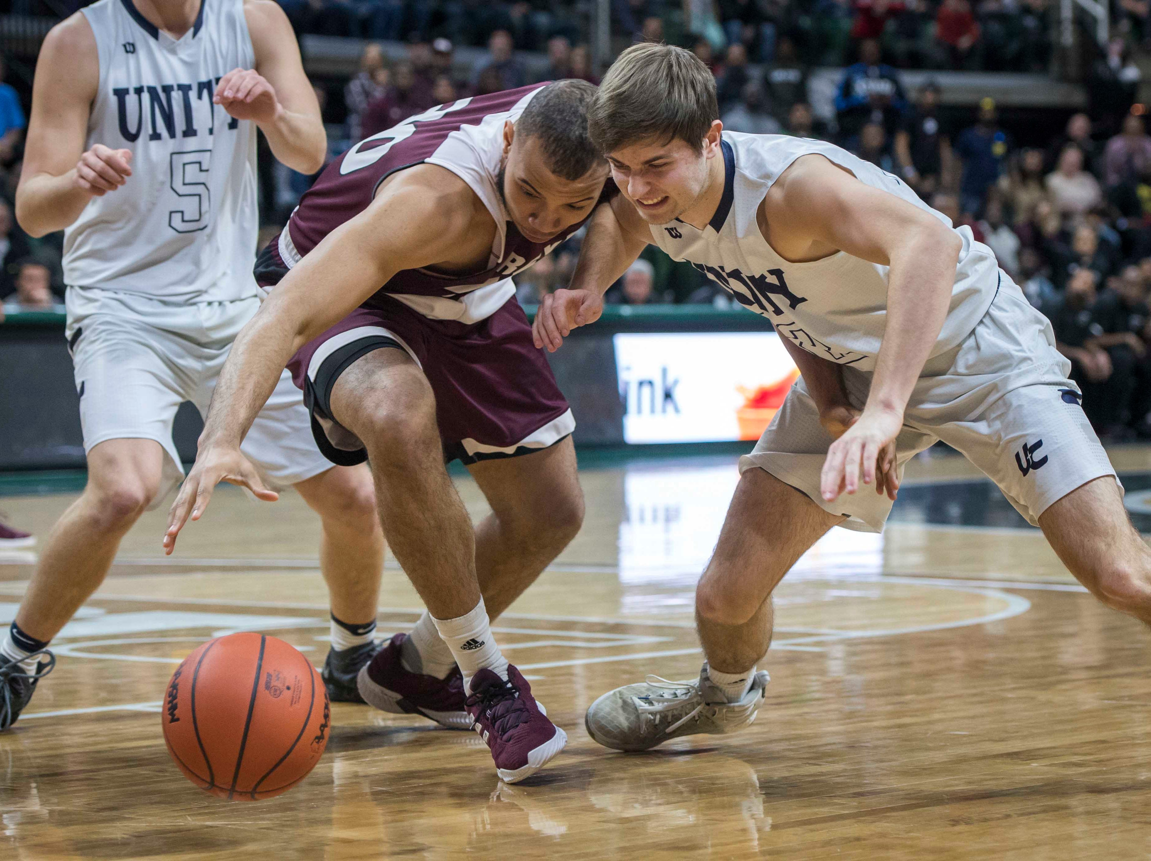 River Rouge's Dan Few and Hudsonville Unity Christian's Ryan Takens fight for a loose ball in the first half.