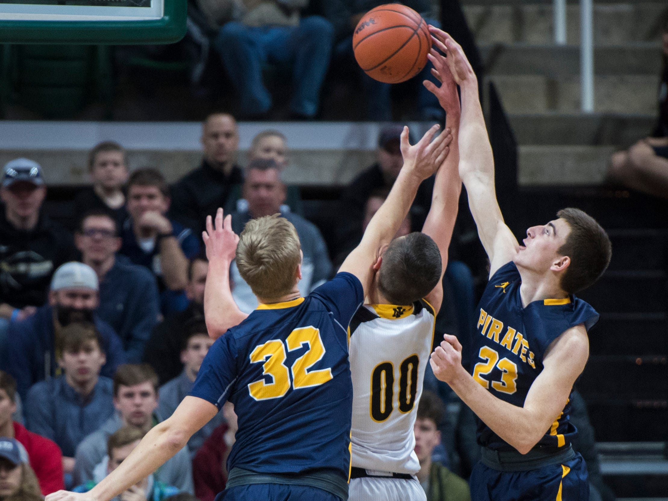 From left, Pewamo-Westphalia's Andre Smith, Iron Mountain's Foster Wonders and Pewamo-Westphalia's Aaron Bearss jump for a loose ball in the first half.