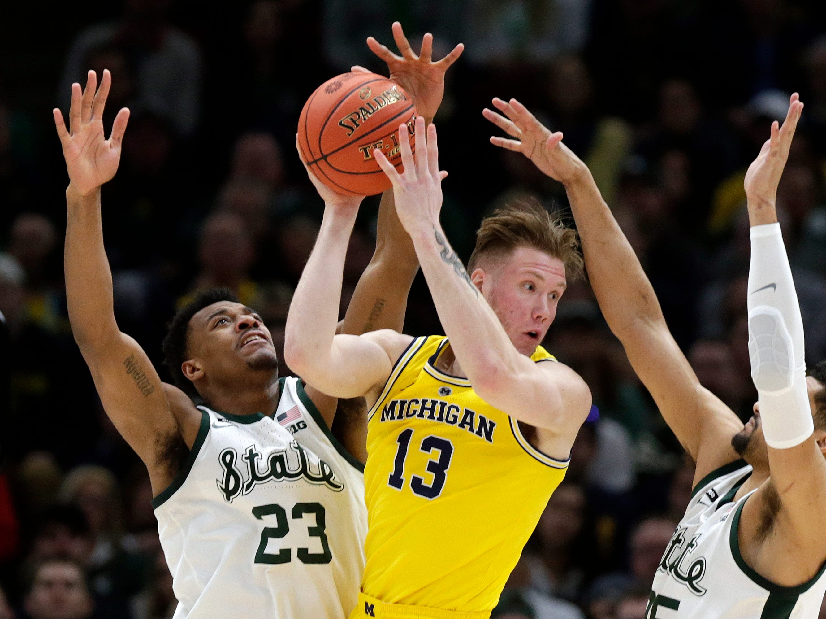 Michigan's Ignas Brazdeikis (13) looks to pass the ball against Michigan State's Xavier Tillman (23) and Kenny Goins (25) during the first half of an NCAA college basketball championship game in the Big Ten Conference tournament, Sunday, March 17, 2019, in Chicago.