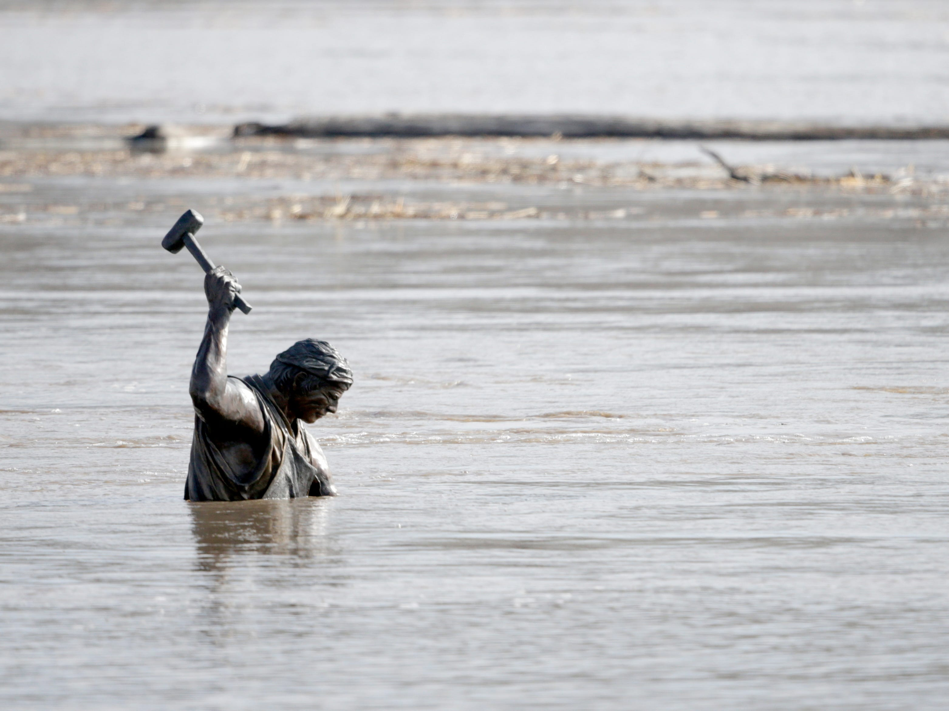 Debris float by as the high waters of the Missouri River almost submerge a blacksmith, part of the Monument to Labor statue by Matthew J. Placzek, in Omaha, Neb., Saturday, March 16, 2019. Thousands of people have been urged to evacuate along eastern Nebraska rivers as a massive late-winter storm has pushed streams and rivers out of their banks throughout the Midwest.