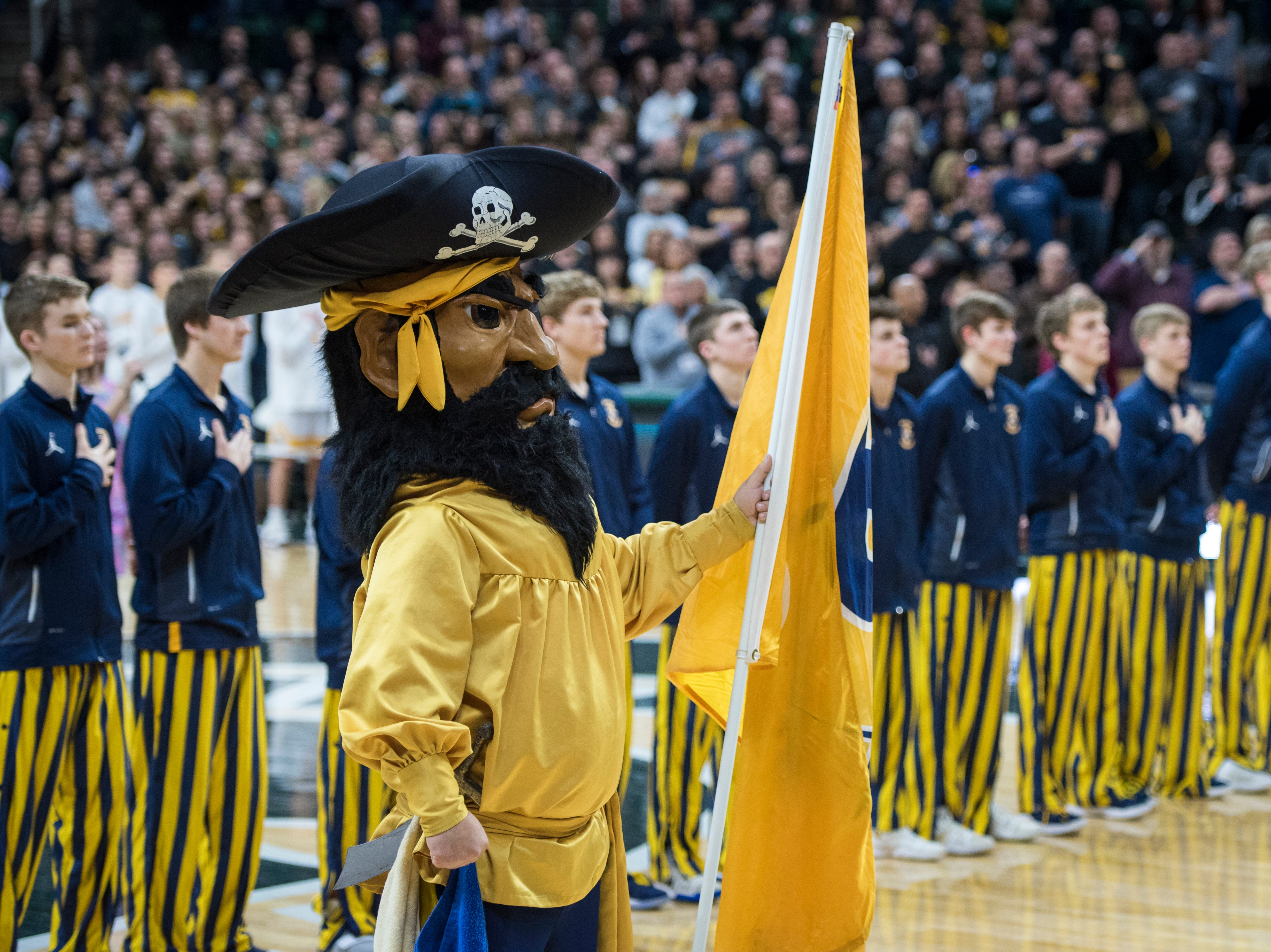 Pewamo-Westphalia's mascot observes the national anthem before the game.