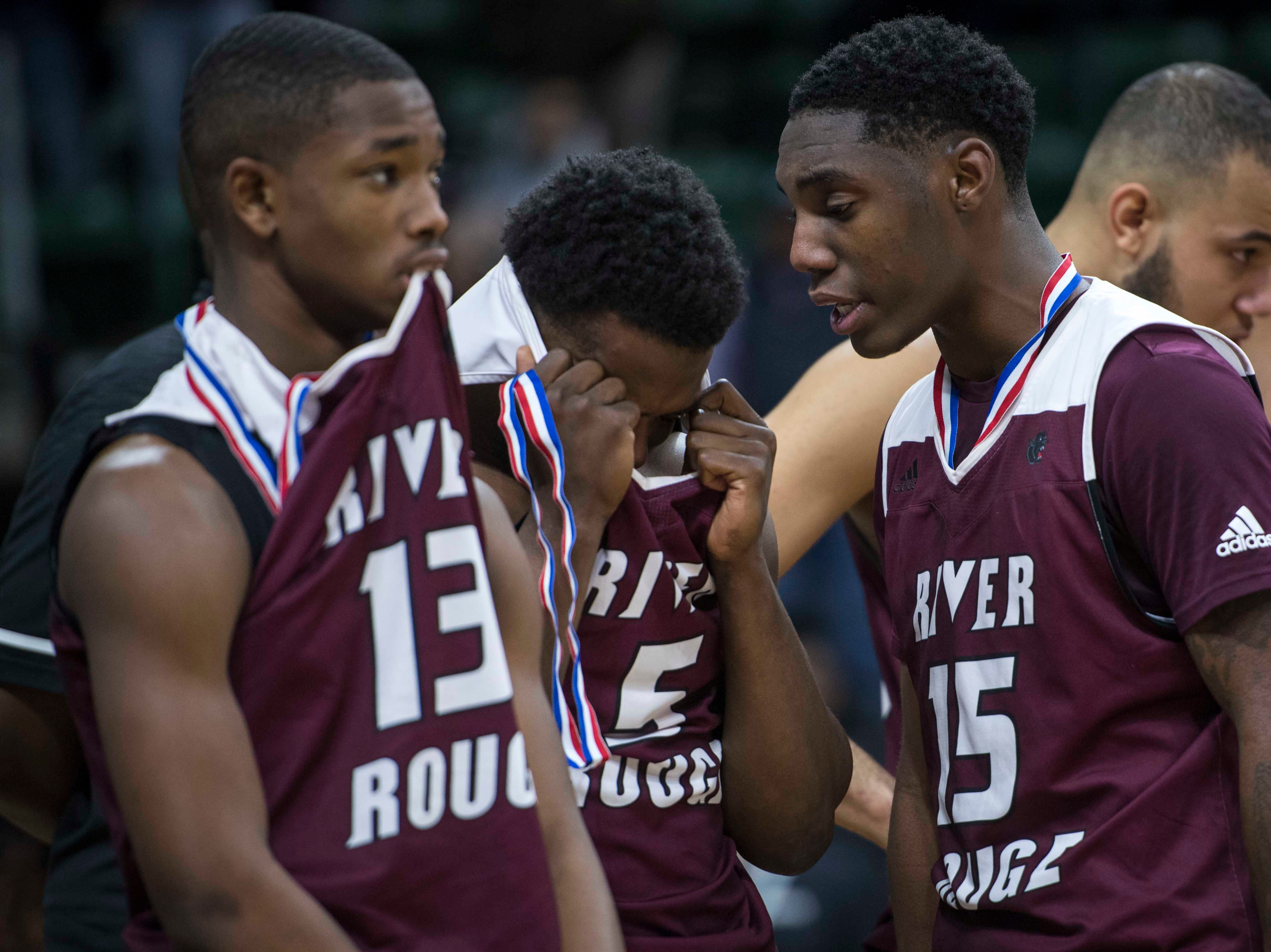 River Rouge's Jalen Holly, left, looks on while teammate Kamal Hadden comforts Jason Norton, right, after their team lost the game.