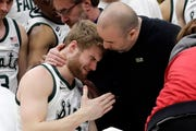 Medical personnel took talks to Michigan State's Kyle Ahrens, left, as Ahrens was the taken out of the court for injury during the first half of Sunday's Big Ten tournament title game.