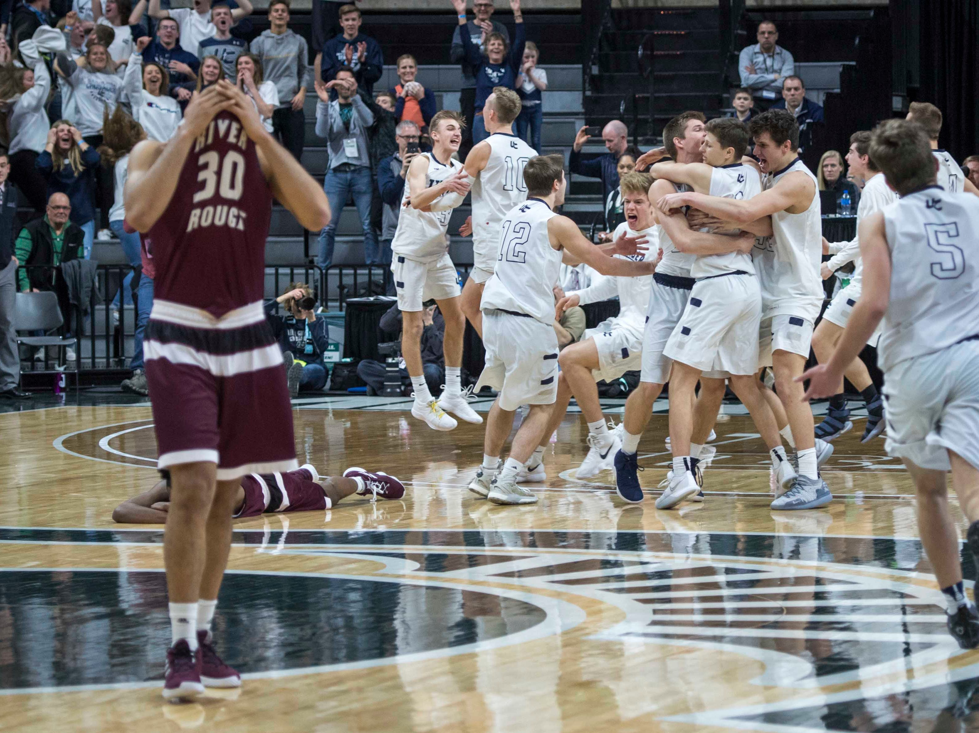 River Rouge's Dan Few buries his head in his jersey while Hudsonville Unity Christian players celebrate their 58-55 Division 2 championship game victory over River Rouge at Breslin Center in East Lansing on Saturday, March 16, 2019.
