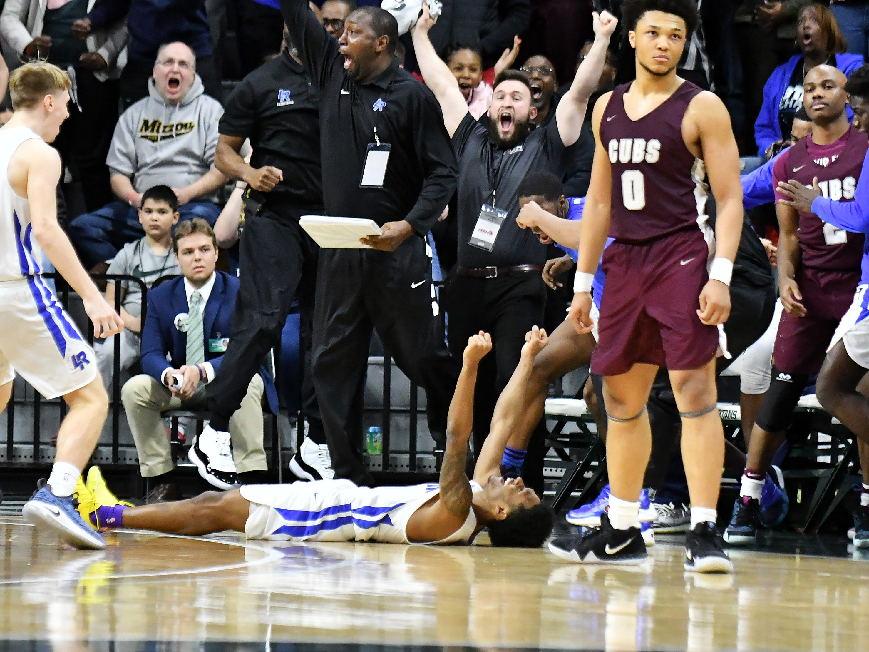 Ypsilanti Lincoln guard Jalen Fisher (14), laying on the floor, reacts after hitting the winning shot at the buzzer in a 64-62 victory over U-D Jesuit in the Division 1 final Saturday, March 16, 2019, at Breslin Center in East Lansing.
