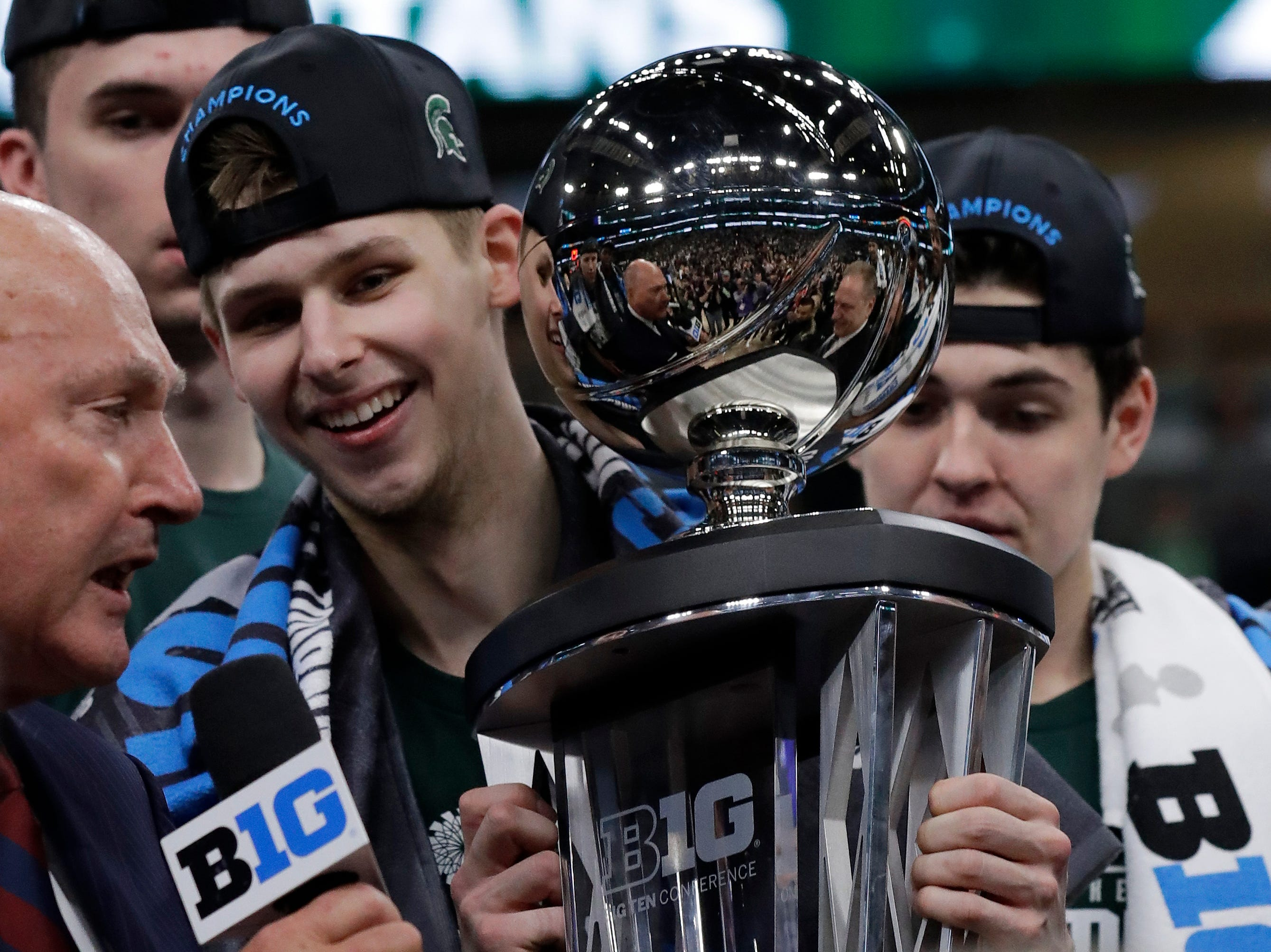 Michigan State's Matt McQuaid holds the championship trophy as he celebrates after defeating Michigan 65-60.