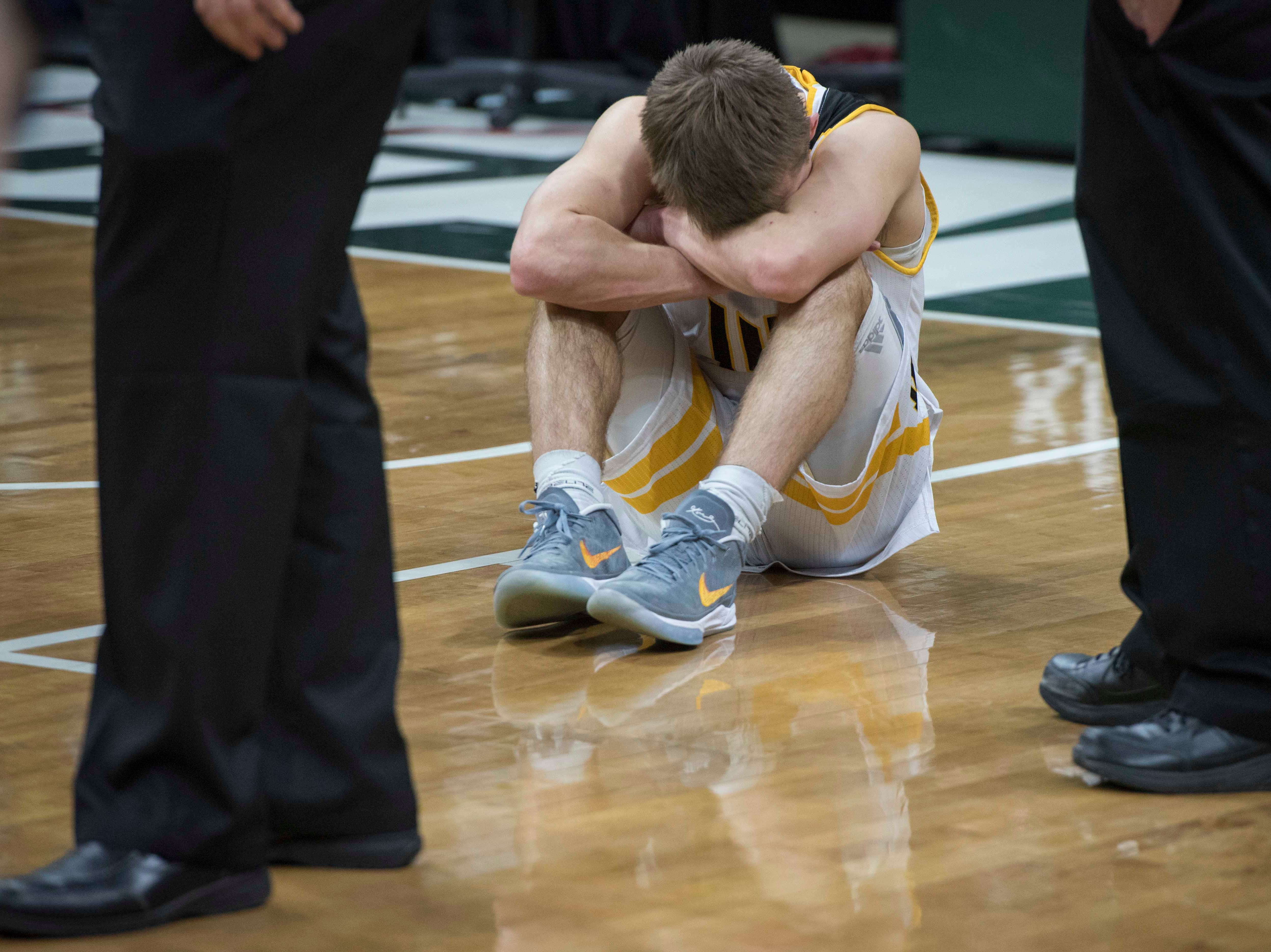 Iron Mountain's Marcus Johnson buries his head after his team lost the game.
