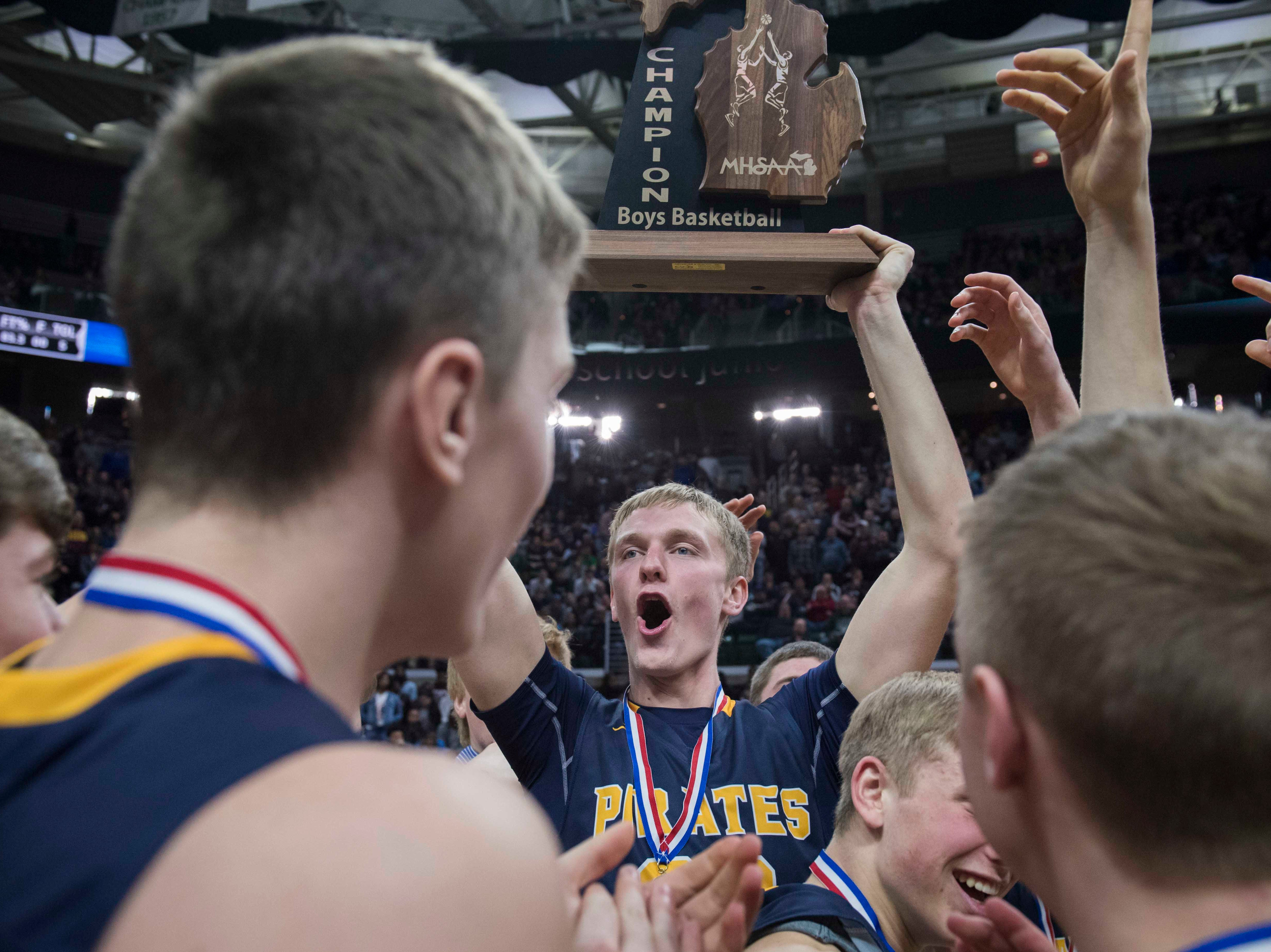 Pewamo-Westphalia's Andre Smith hoists the Div. 3 trophy after the game.