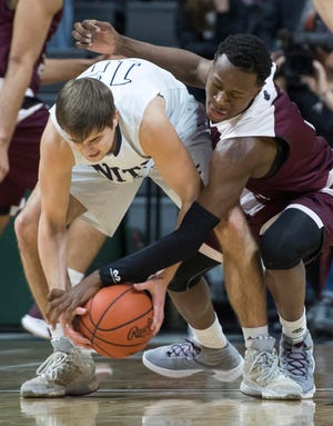 Hudsonville Unity Christian's Ryan Takens and River Rouge's Donavan Freeman reach for a loose ball in the first half.
