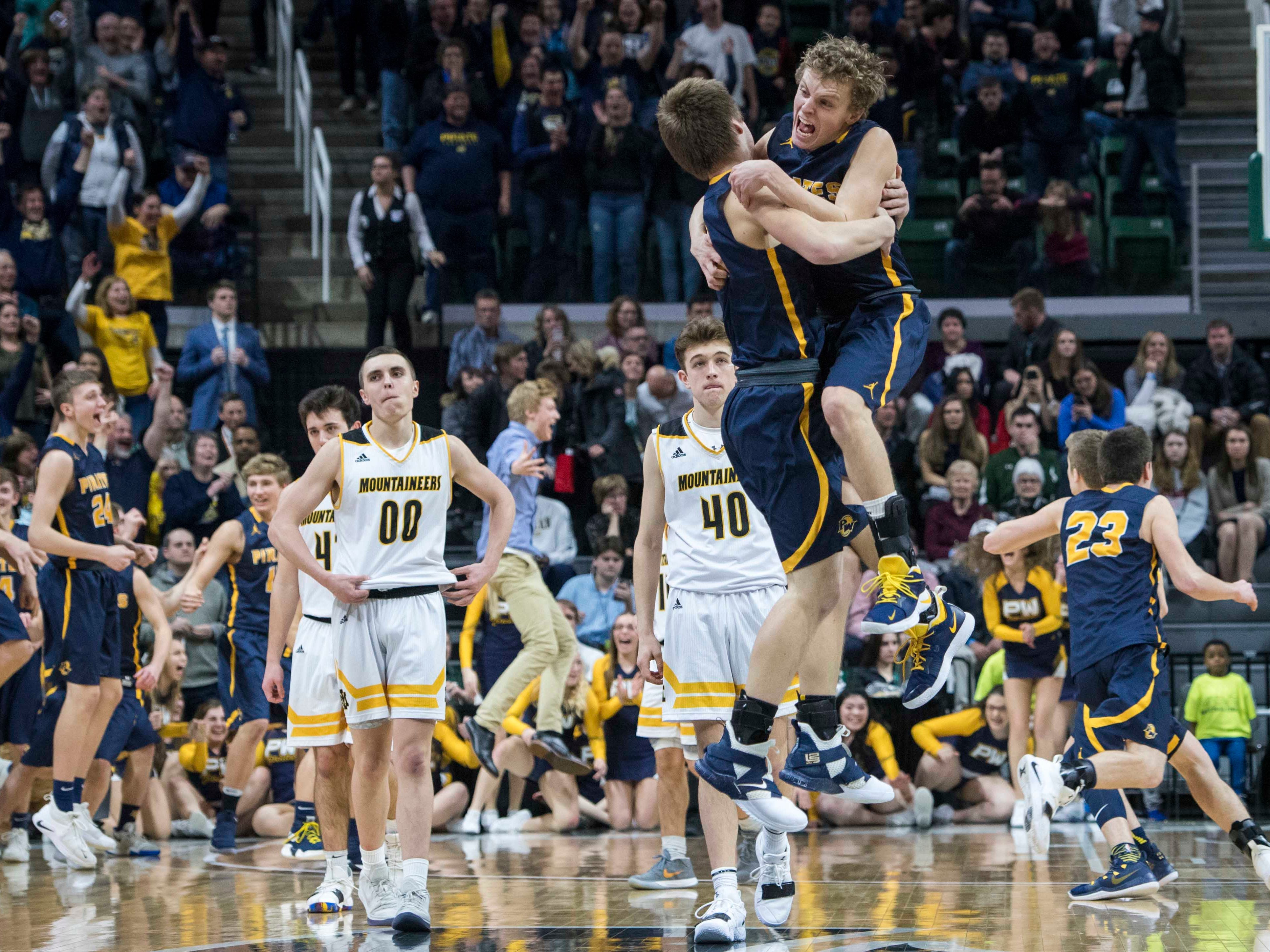 Pewamo-Westphalia's Nathan Wirth, left, and Collin Trierweiler celebrate with a leaping embrace after Trierweiler made the game-winning basket to defeat Iron Mountain 53-52 in the MHSAA Div. 3 championship game at Breslin Center in East Lansing on Saturday, March 16, 2019.