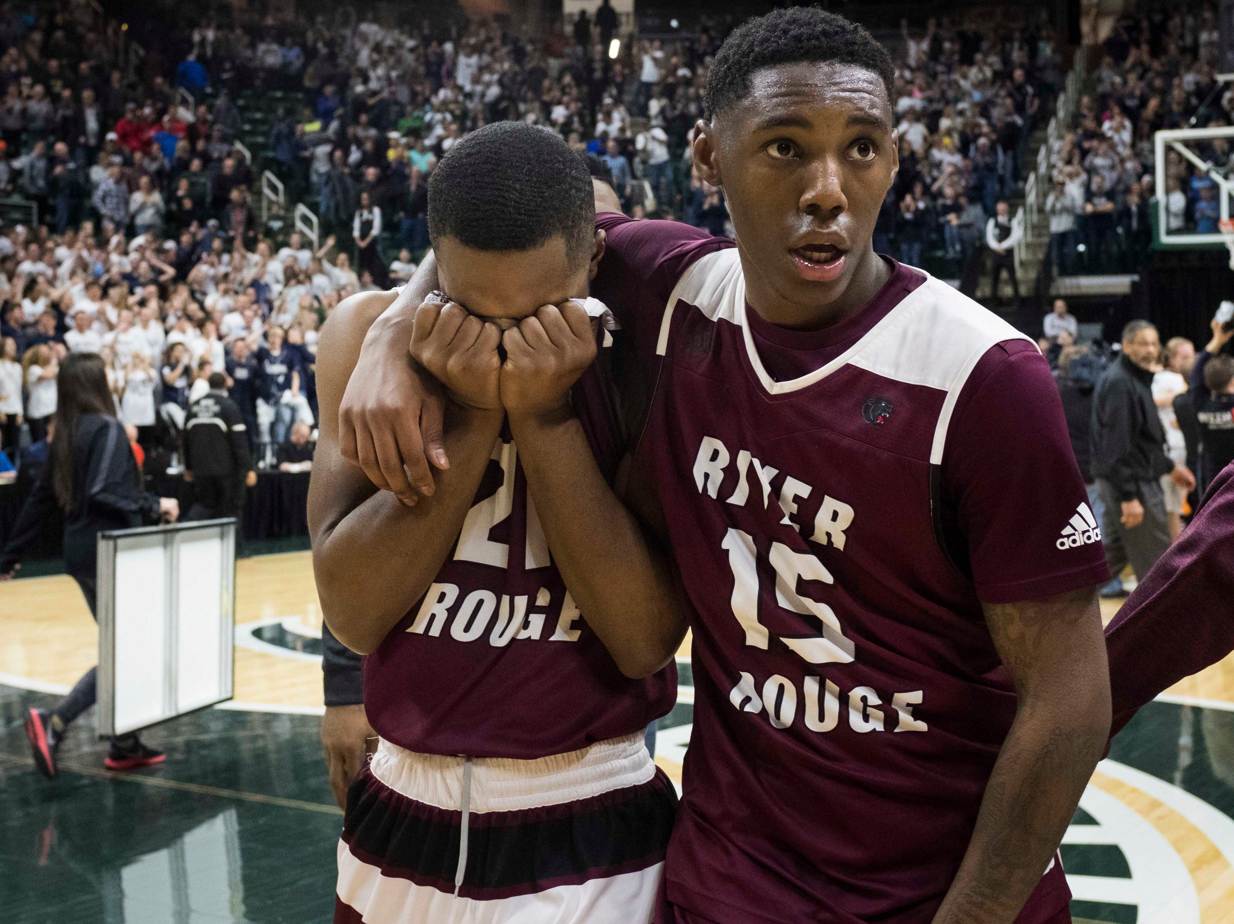 River Rouge's Nigel Colvin buries his face in his hands while teammate Kamal Hadden comforts him as they walk off the floor after losing in the Division 2 championship game.