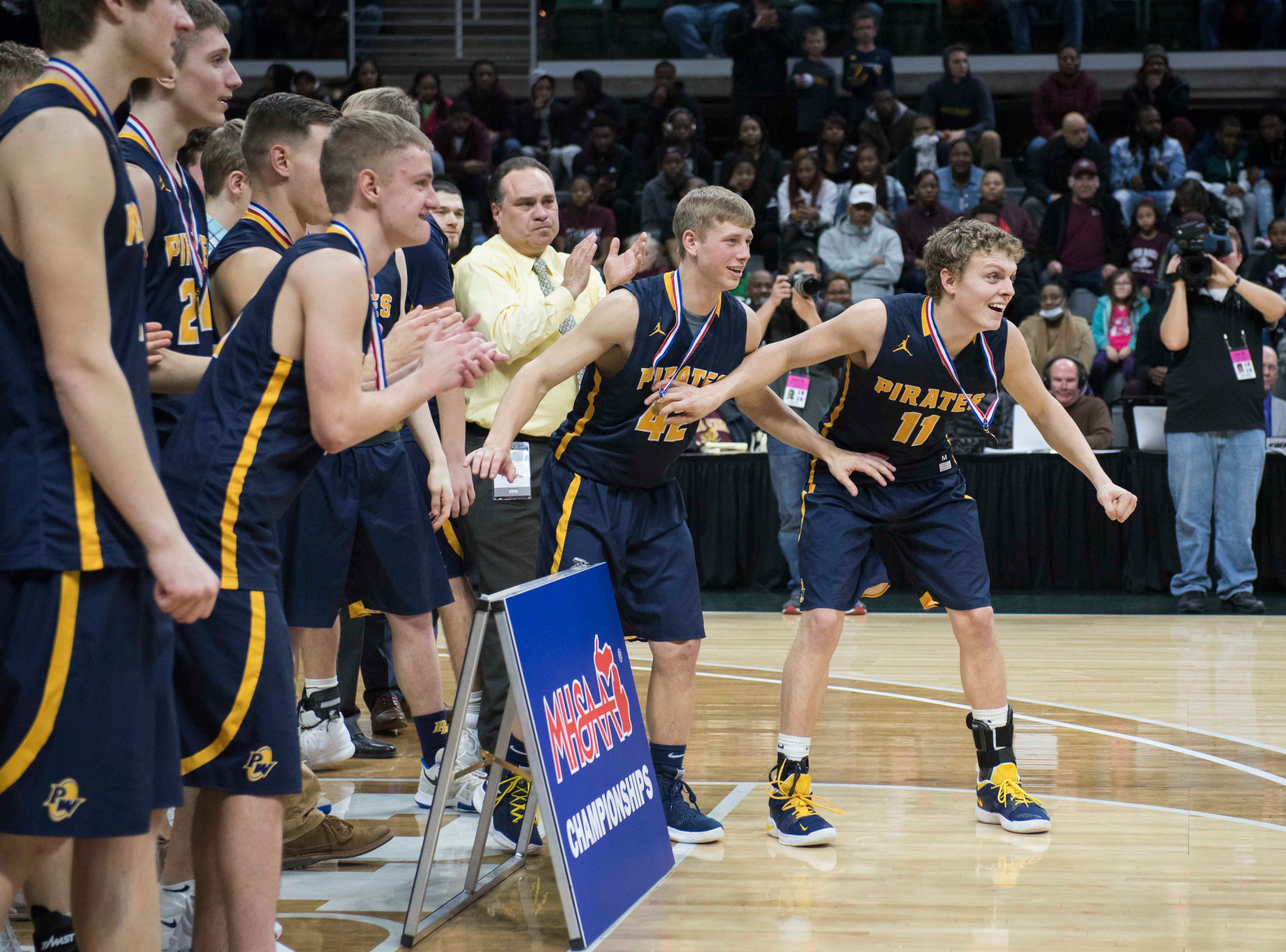 Pewamo-Westphalia players inch up before receiving the Division 3 championship trophy.