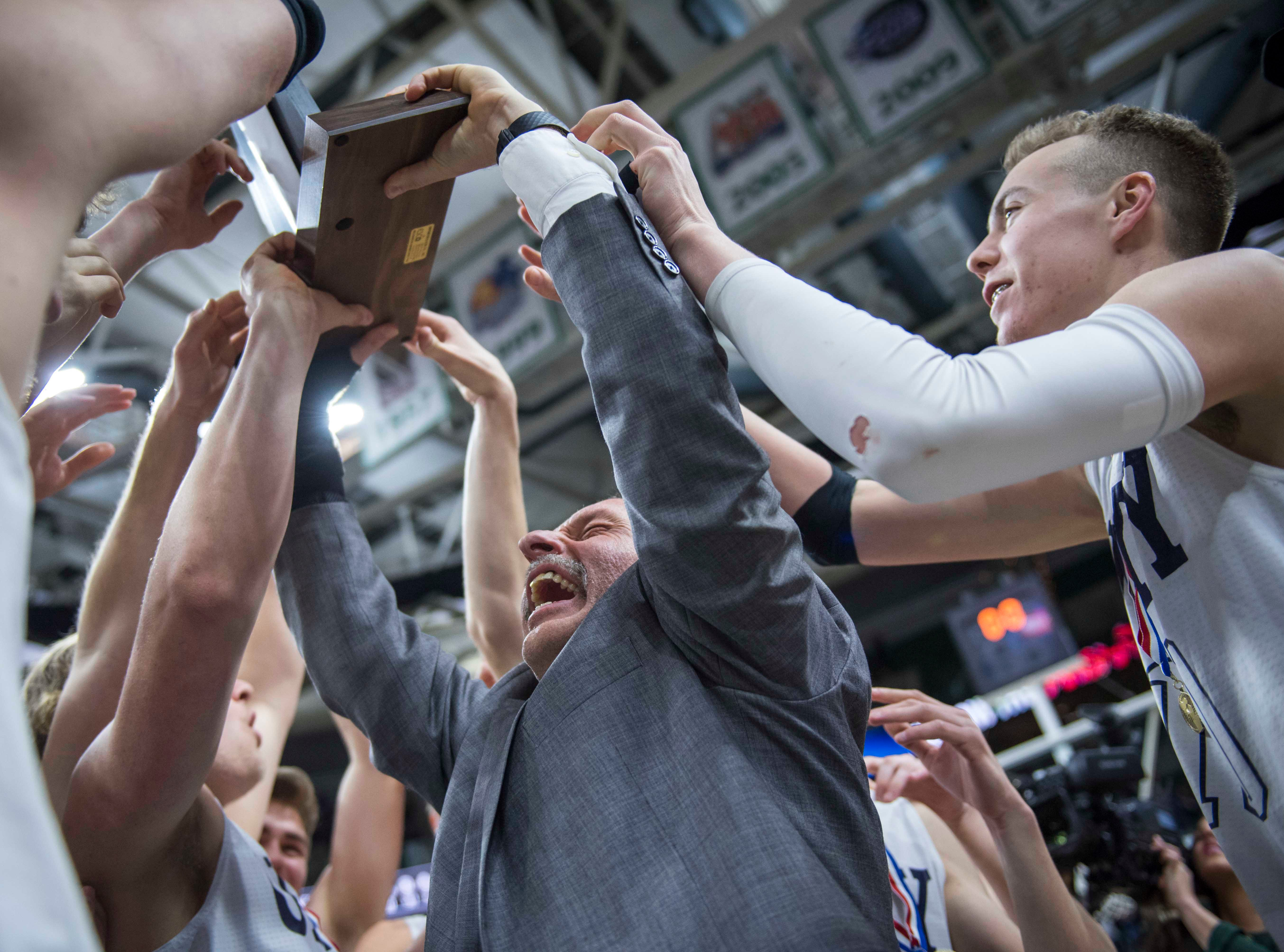Hudsonville Unity Christian's head coach Scott Soodsma hoists the championship trophy after his team won the game.